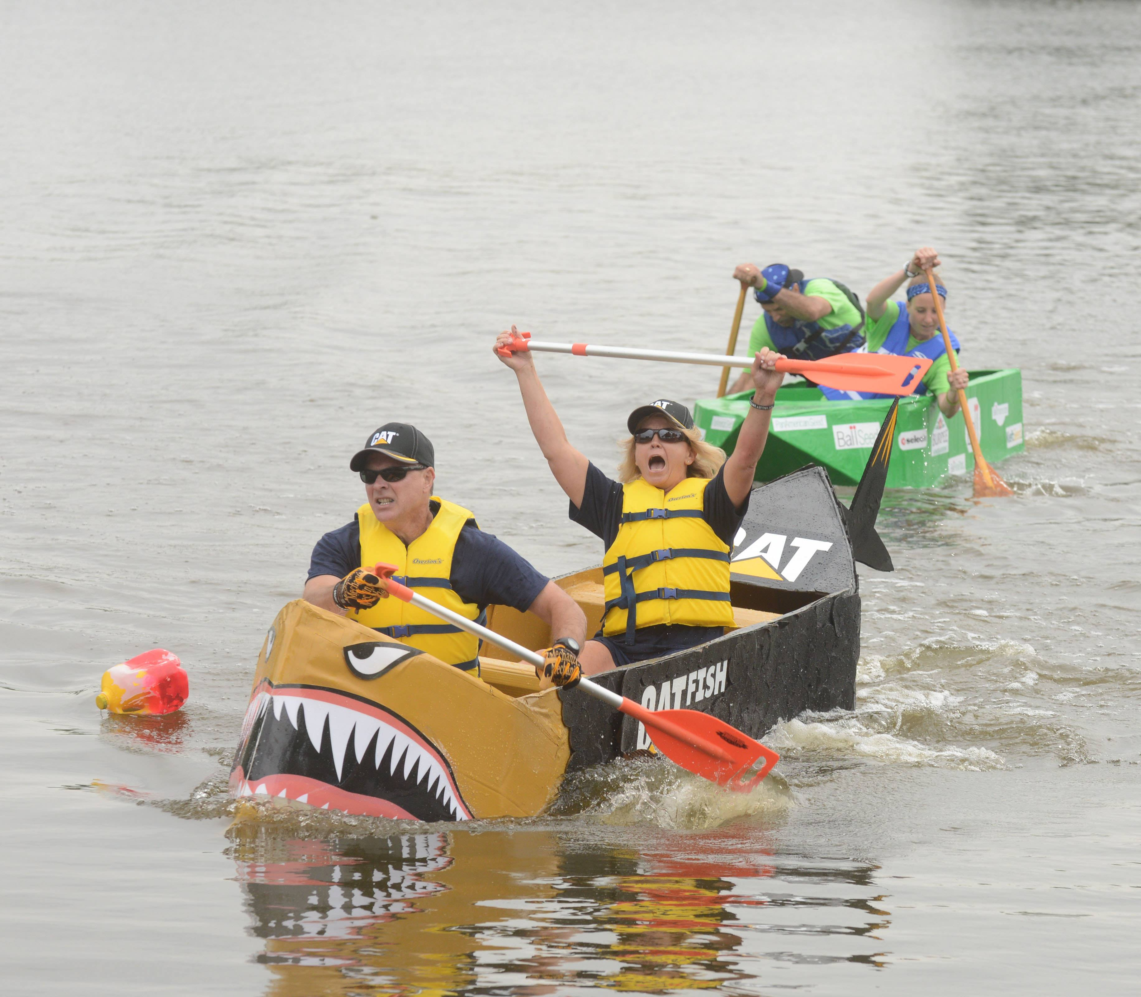 Mary Moutray lifts her arms in victory while Don Bauer continues to row as the Aurora duo won their heat Saturday during the Fox Valley United Way's 12th Annual Cardboard Boat Race at Phillips Park.