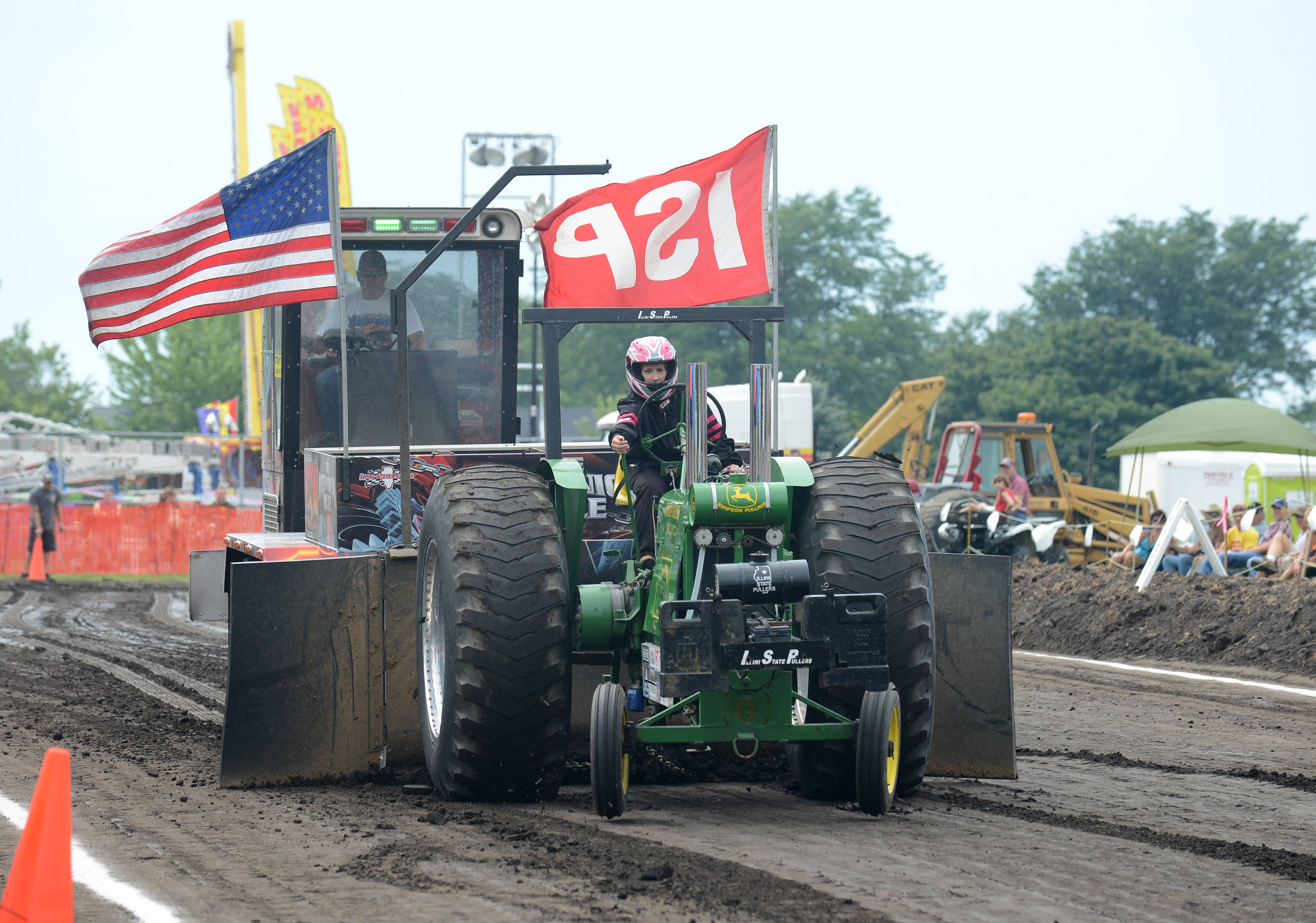 "Lara Tuma of Paw Paw competes in the 5,000 NA SS class tractor pull with a '40 John Deere G 2-cylinder tractor named ""2 is Enough"" at Elburn Days Saturday. This is her first year competing."