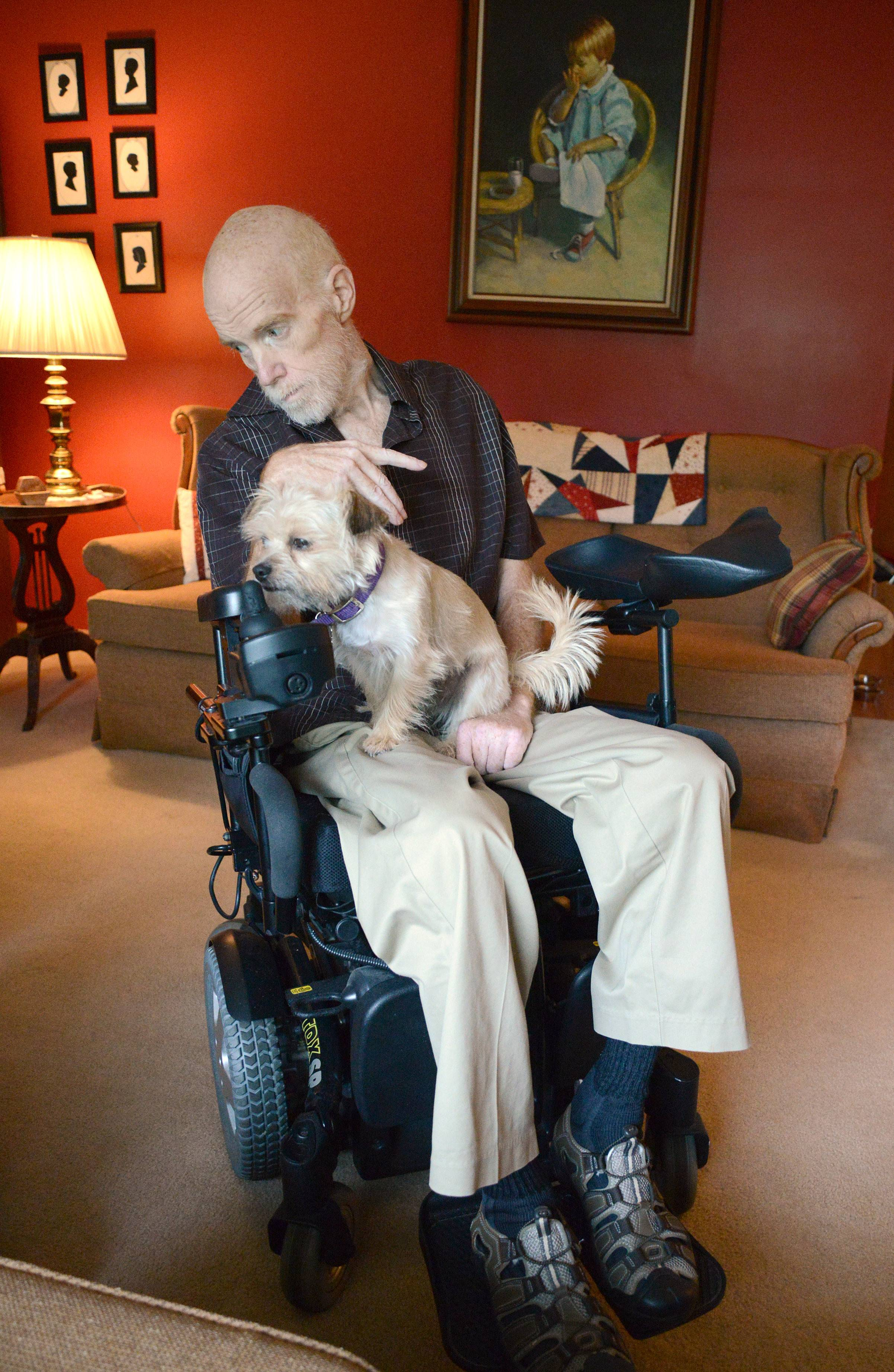 Elli, the family dog, keeps Tom Linder company in their Elgin home.