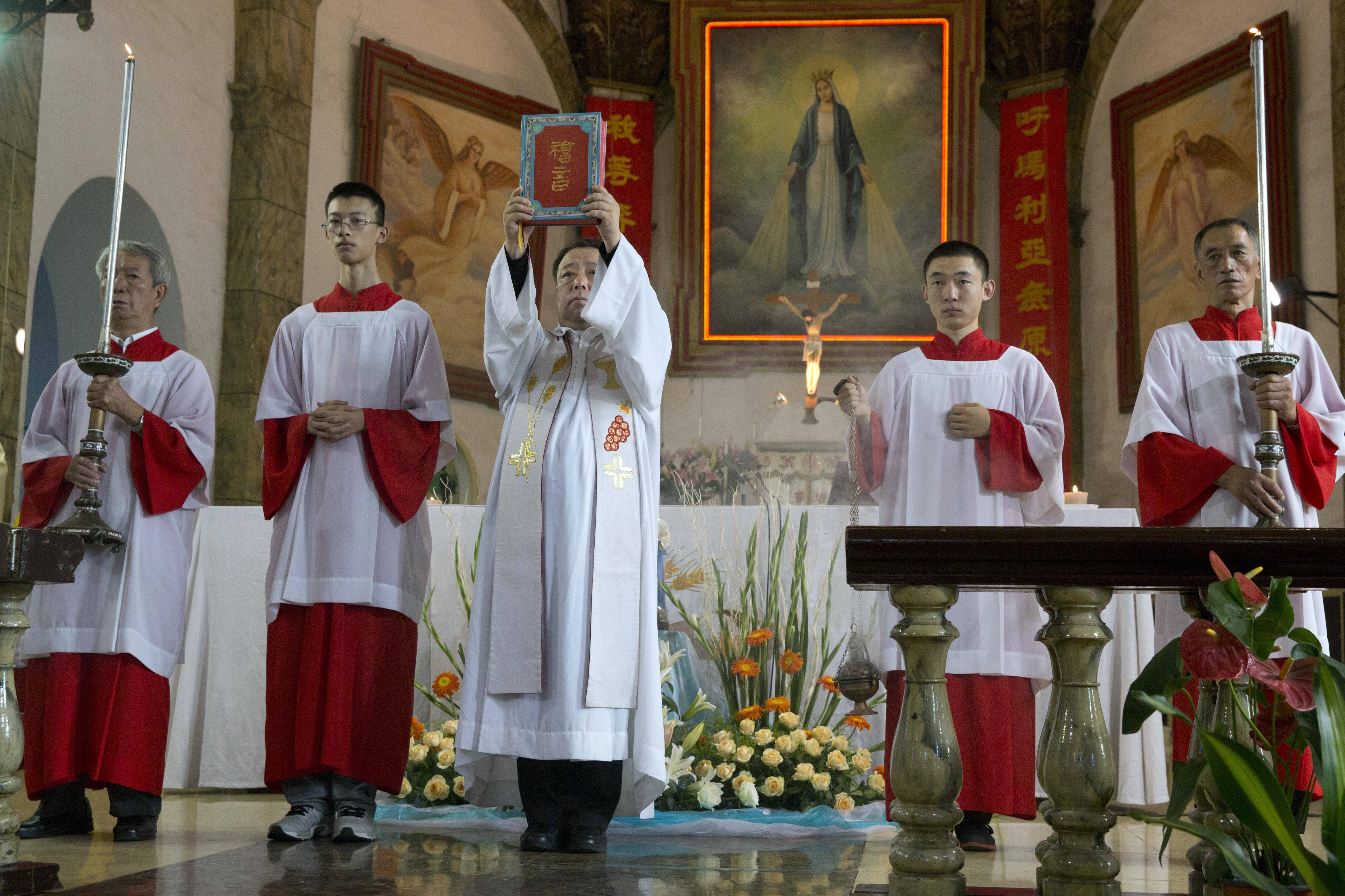 A Chinese priest holds up a bible during a mass at the 400-year-old Cathedral of the Immaculate Conception in Beijing, China, Friday, Aug. 15. Chinese Catholics on Friday cheered Pope Francis' visit to neighboring South Korea, saying they hoped his trip to their region would help end the estrangement between Beijing and the Vatican. However, China's entirely state-run media imposed a virtual news blackout on his visit, ensuring the public at large would know little about Francis' activities.