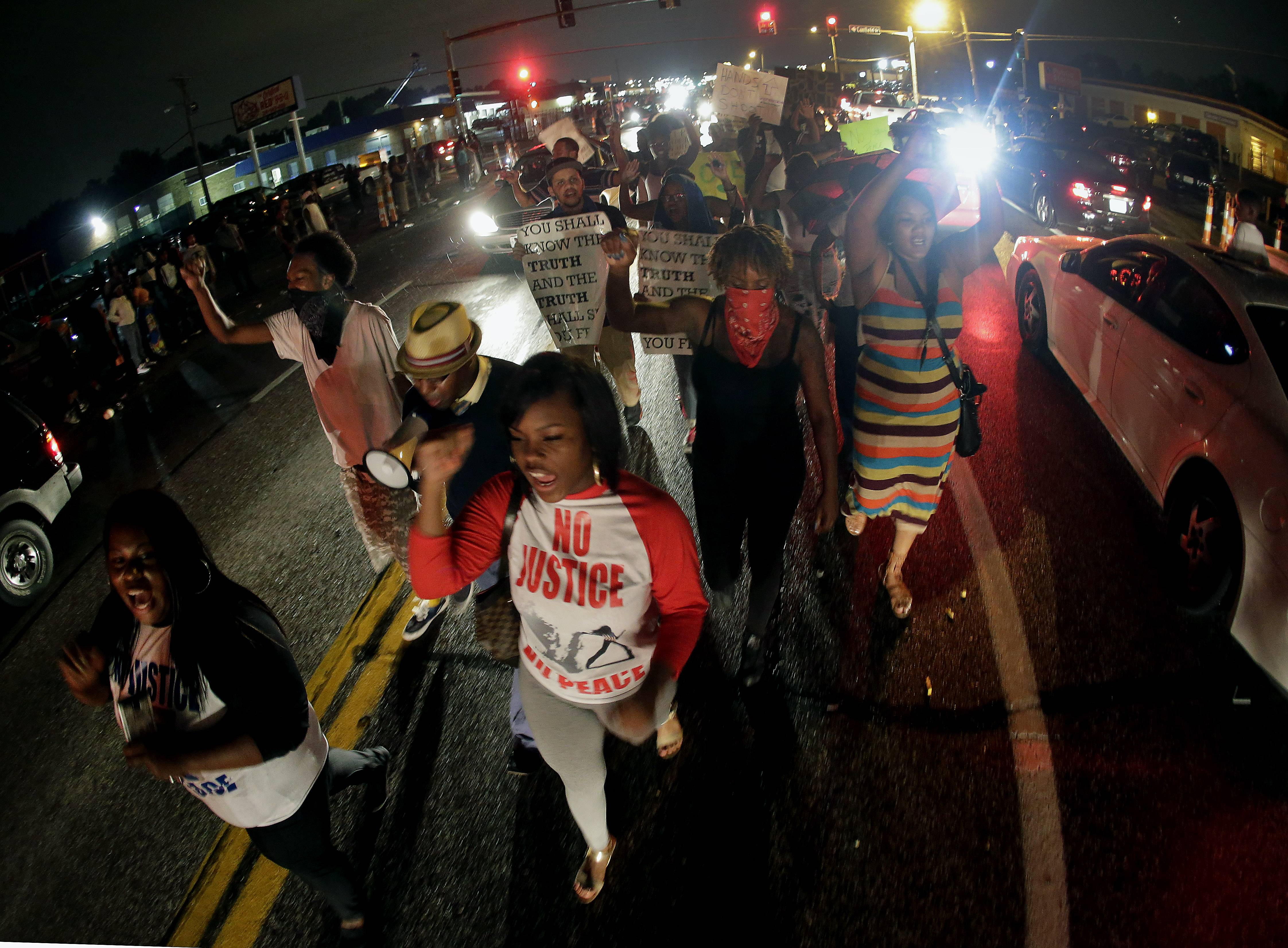 Protesters march down the middle of a street, Friday, Aug. 15, in front of a convenience store that was looted and burned following the shooting death of Michael Brown by police nearly a week ago in Ferguson, Mo.
