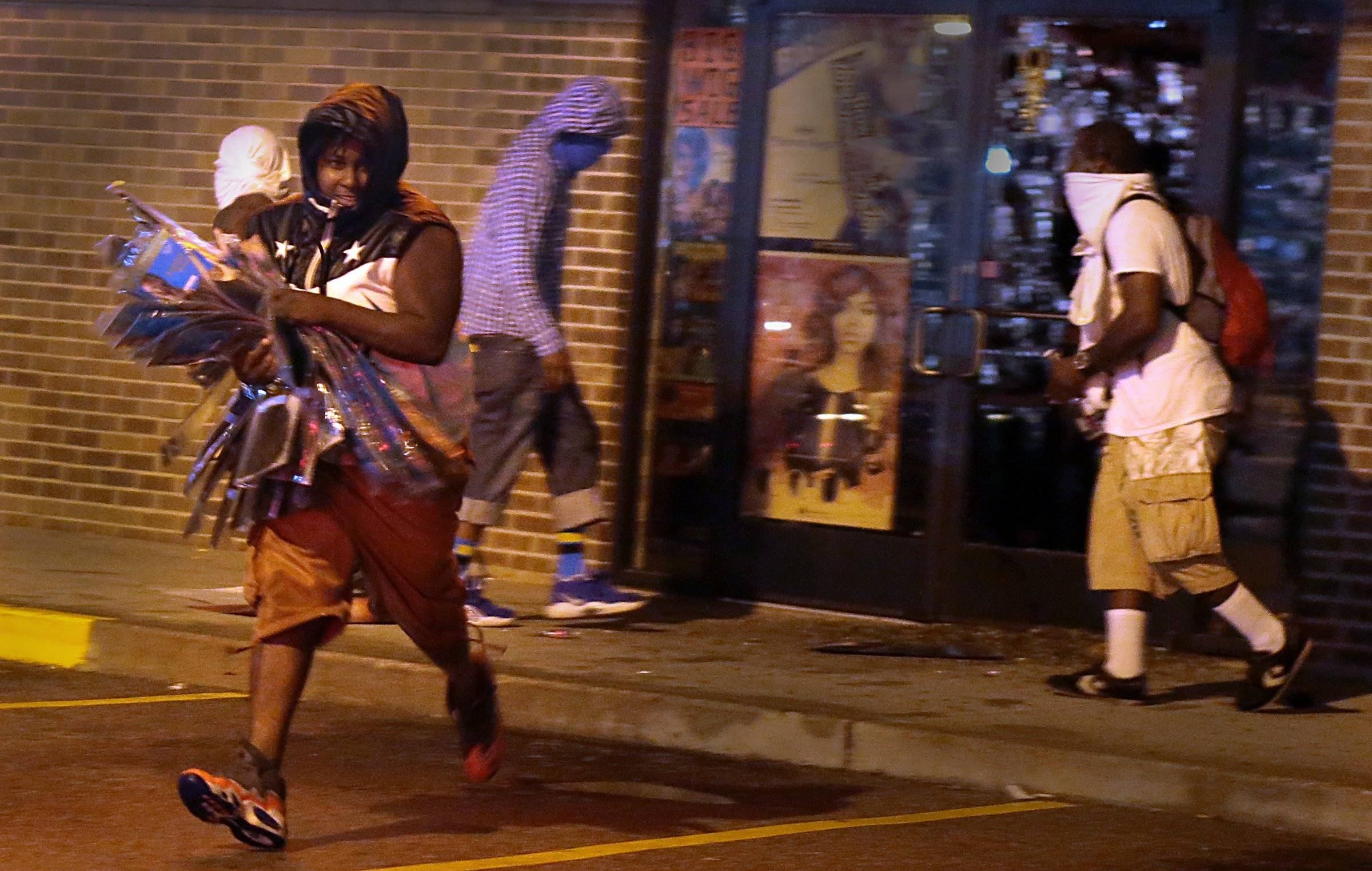 A looter escapes with items from Feel Beauty Supply on West Florissant Avenue in Ferguson early Saturday, Aug. 16, after protesters clashed with police.