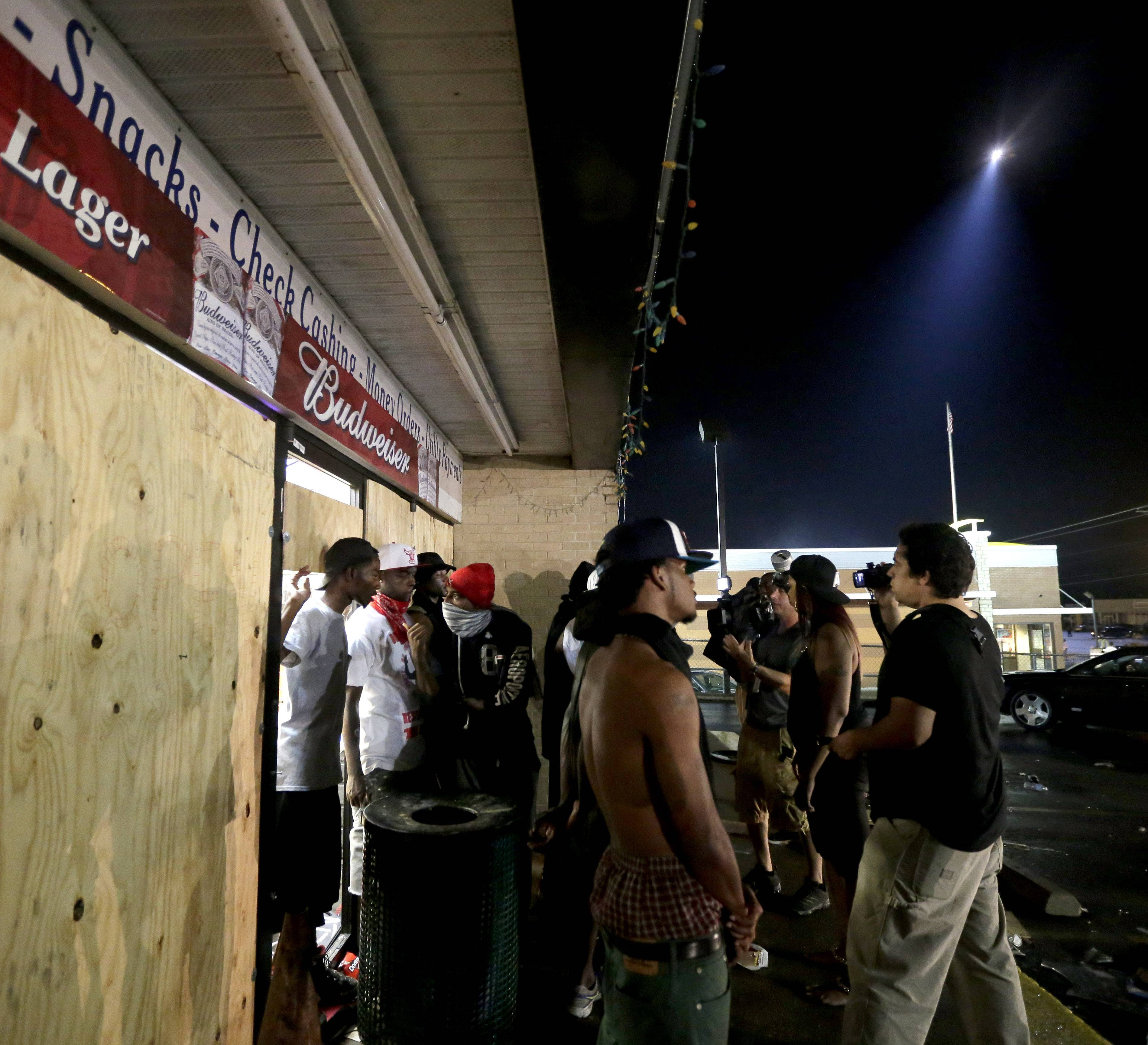 People stand in front of a convenience store after it was looted early Saturday, Aug. 16, in Ferguson, Mo. The violence stemmed from the shooting death of Michael Brown by police a week ago after the teen allegedly stole a box of cigars from the store.