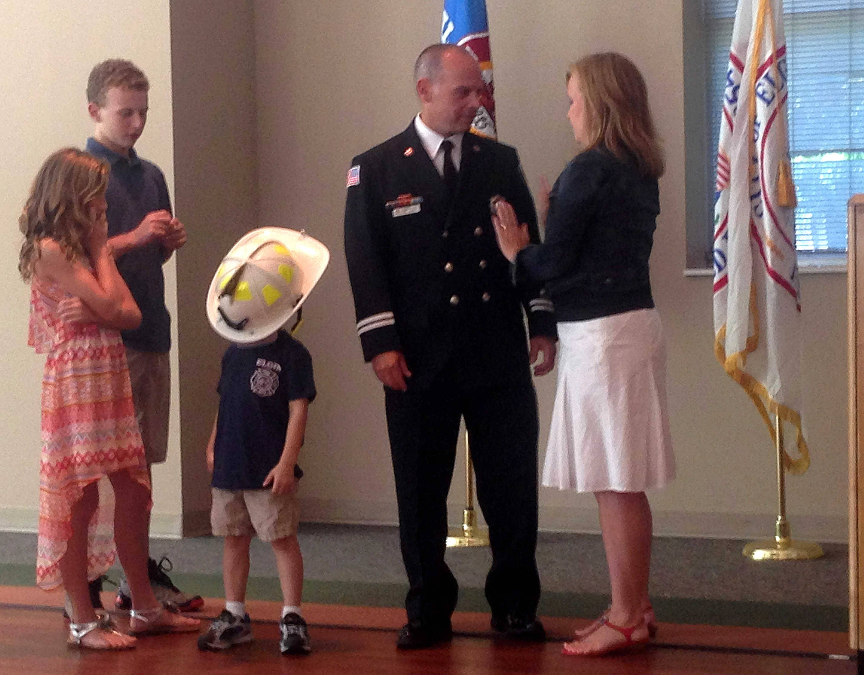 Newly promoted Elgin Fire Capt. Dan Rink looks at his wife, Jennifer, after she pinned his badge at his promotion ceremony Friday at The Centre of Elgin. Their children are, from left, Kendall, Kevin and Alex.