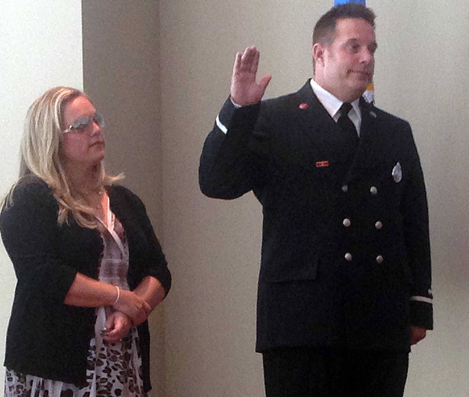 Elgin firefighter Dave Gartrell, with his wife, Kristen, is sworn in as lieutenant by Elgin City Clerk Kim Dews at a ceremony Friday at The Centre of Elgin.