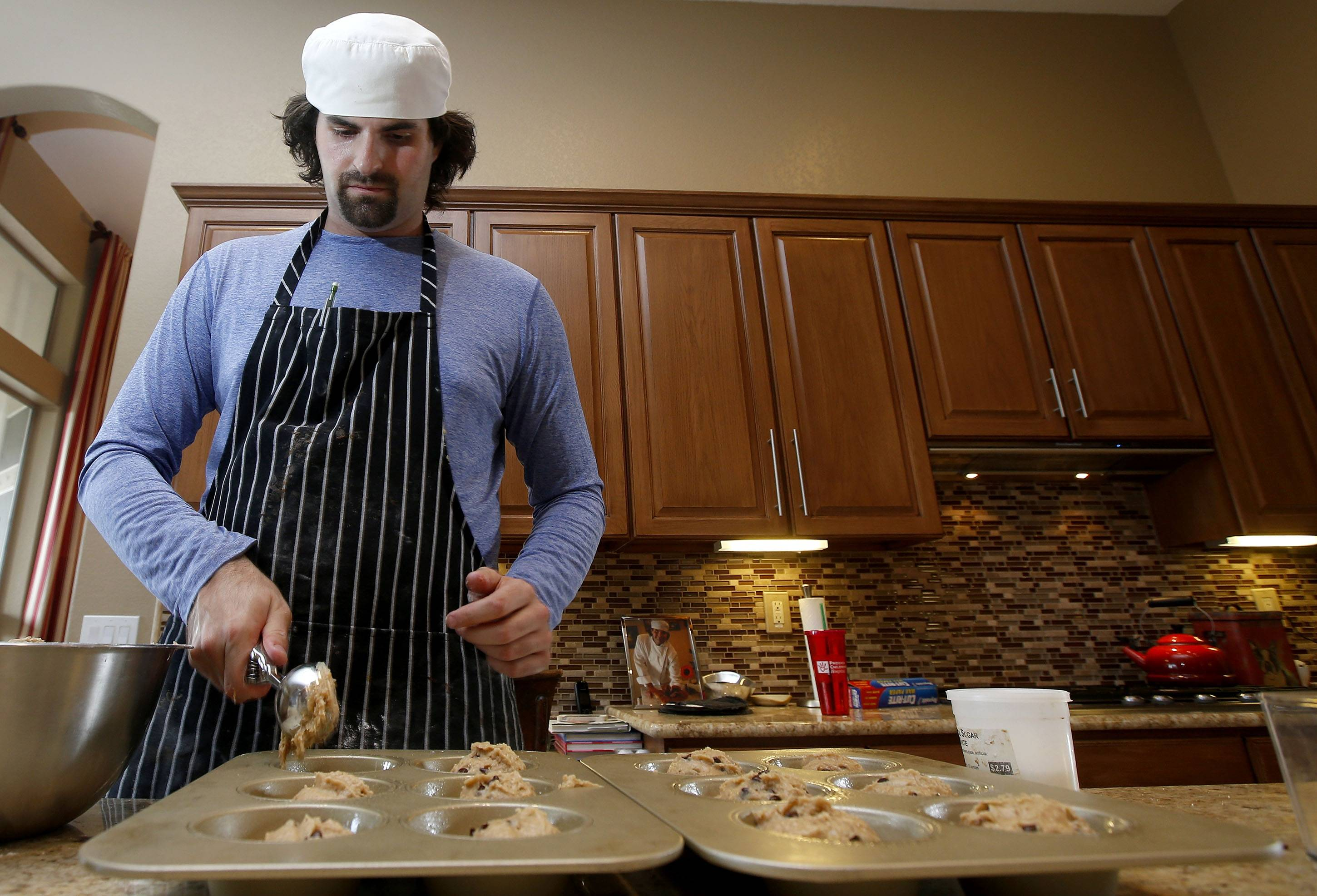 Matt Cottle, owner of Stuttering King Bakery, works a new batch of chocolate chip banana muffins in his parents' kitchen in Scottsdale, Ariz.