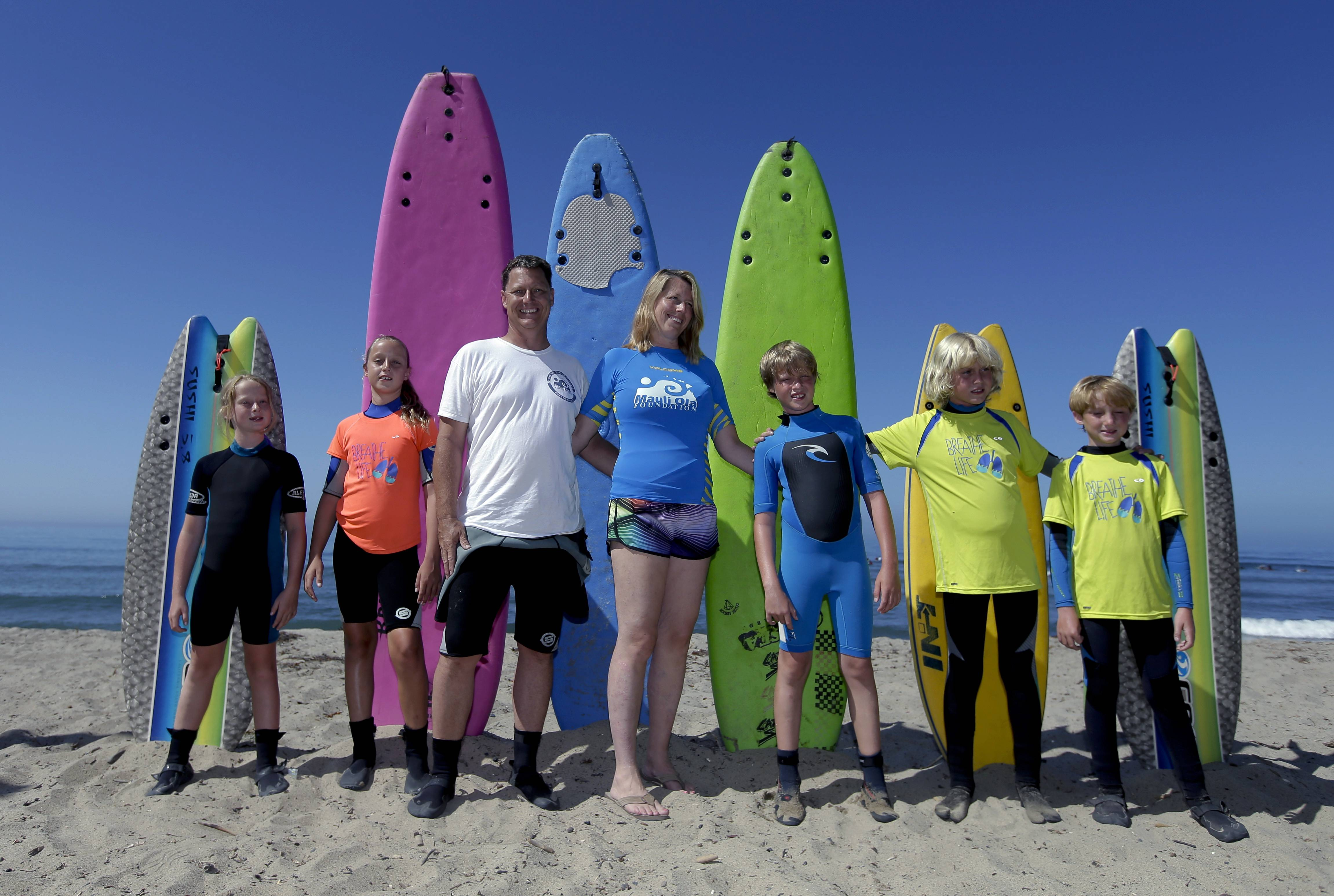 In this July 24, 2014 photo, the Montelone family, from left, Grace, 8, Brooke, 10, Rob, Paulette, Brian, 10, Michael, 12, and Gavin, 8, pose for a family picture on the beach in San Clemente, Calif. Three of the Montelone's five children, who have cystic fibrosis, are part of a growing number of people to take advantage of the health benefits that come with surfing.