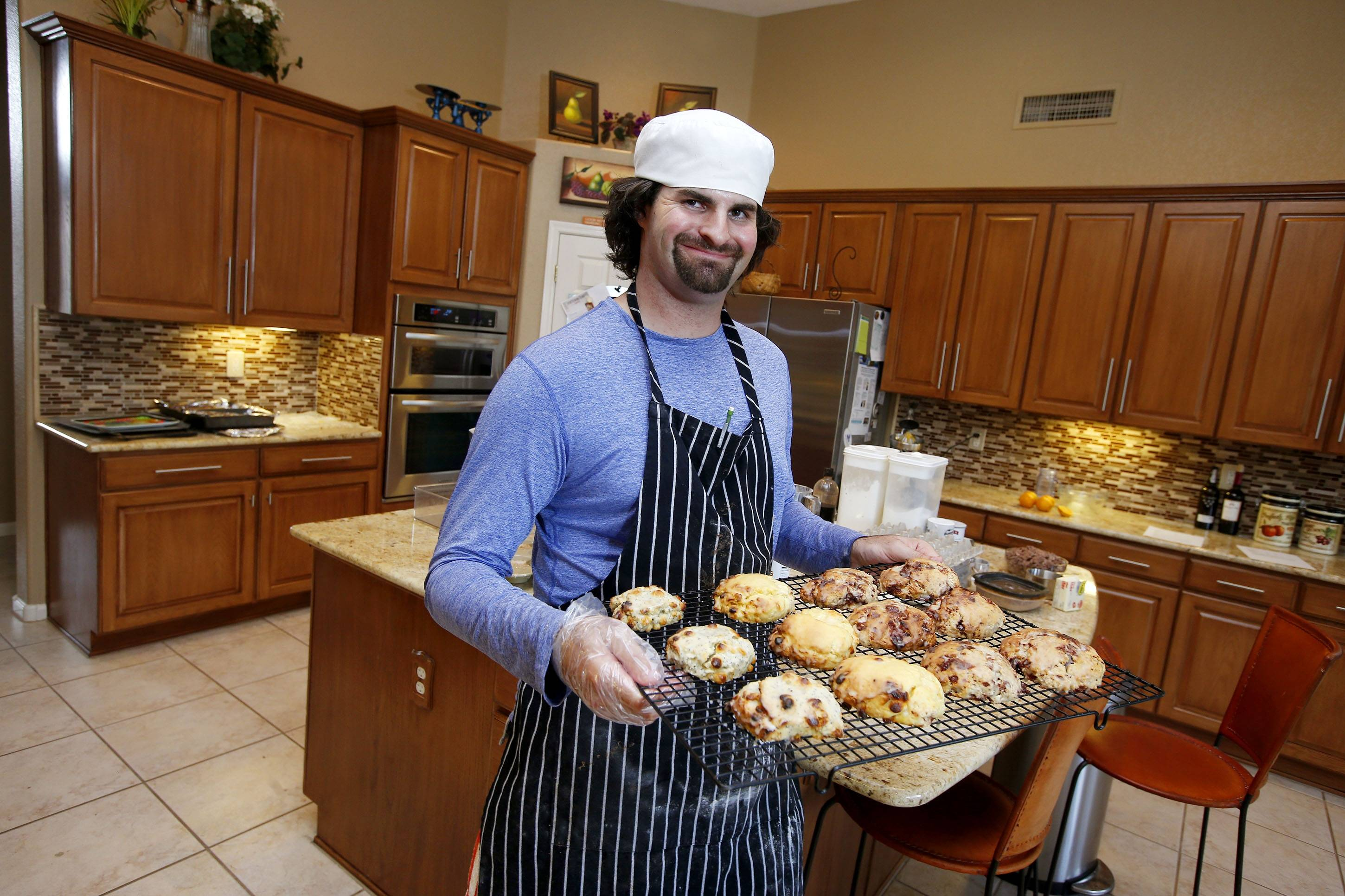 In this July 15, 2014 photo, Matt Cottle, owner of Stuttering King Bakery, smiles as he holds a tray of his scones in his parents' kitchen in Scottsdale, Ariz. Cottle is one of a few known small business owners with autism, a brain disorder that affects a person's ability to comprehend, communicate and interact socially.