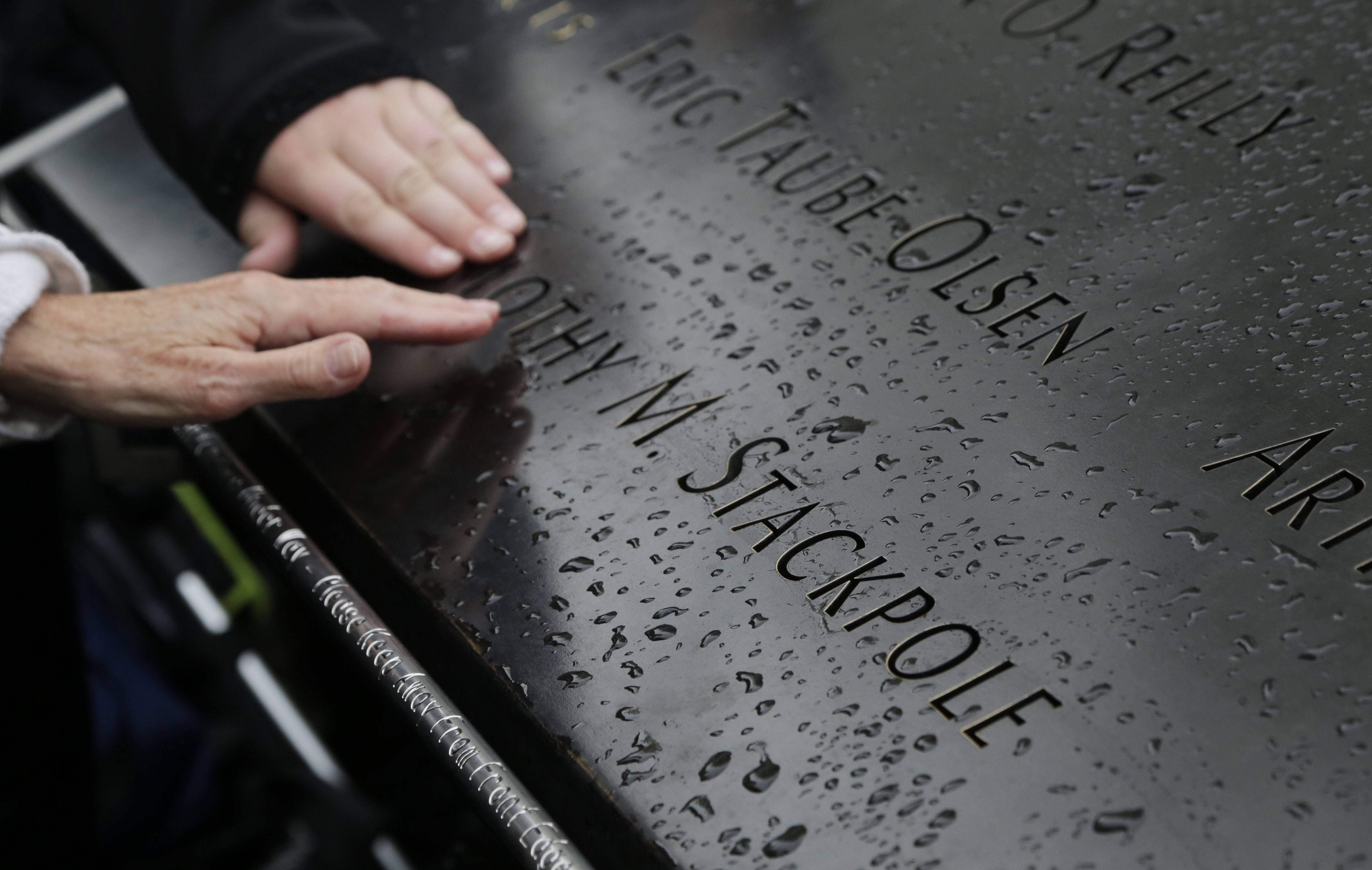 Visitors touch the engraved name of a victim of the Sept. 11, 2001, attacks at the National September 11 Memorial & Museum in New York. The memorial has been visited by nearly 15 million people since it opened three years ago on the footprints of the twin towers.