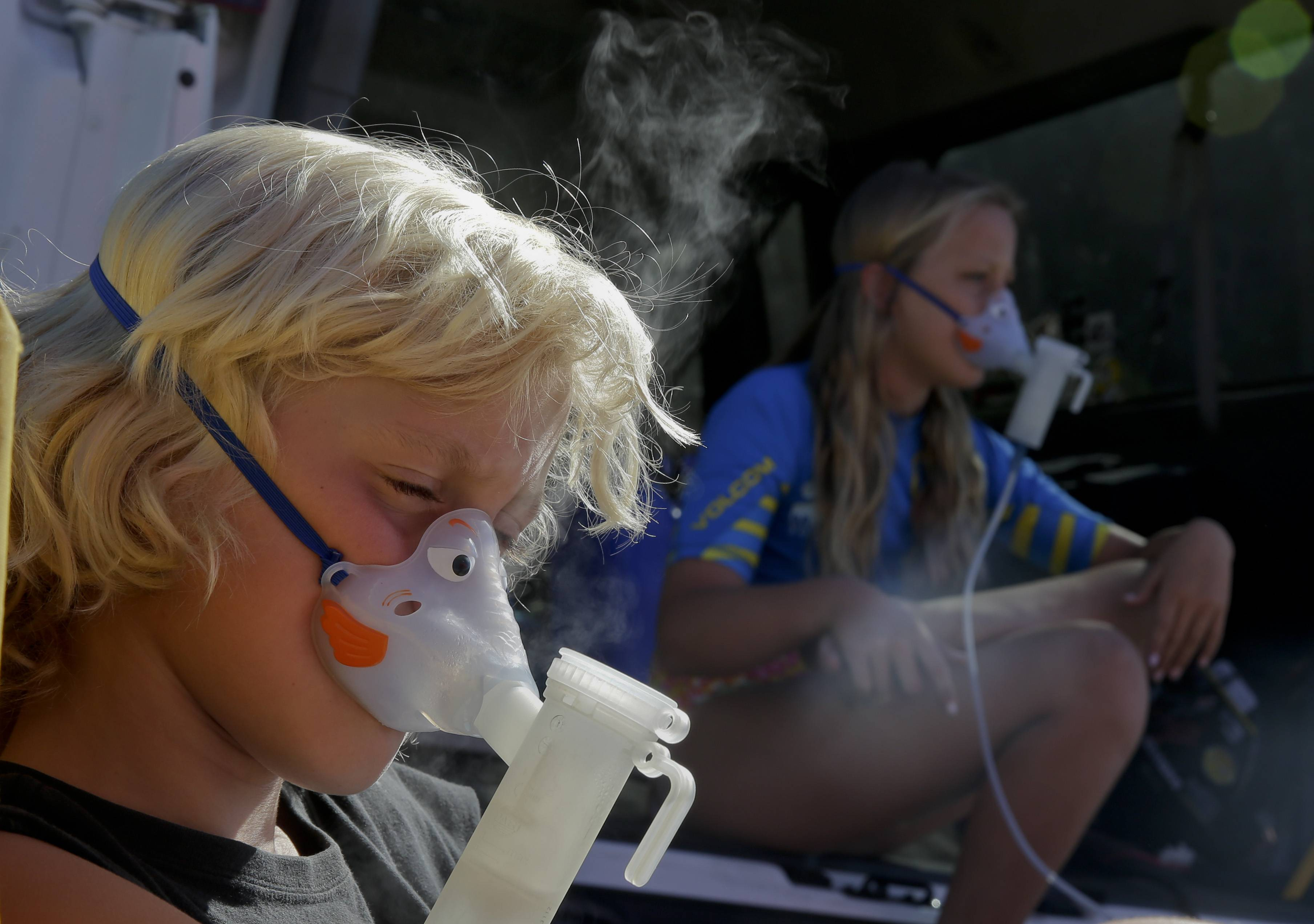 In this July 24, 2014 photo, from left, 10-year-old siblings Michael Montelone, left, and Brooke Montelone, do breathing treatments before heading into the surf in San Clemente, Calif. The children are part of a growing number of people with cystic fibrosis who are taking advantage of the health benefits that come with surfing.