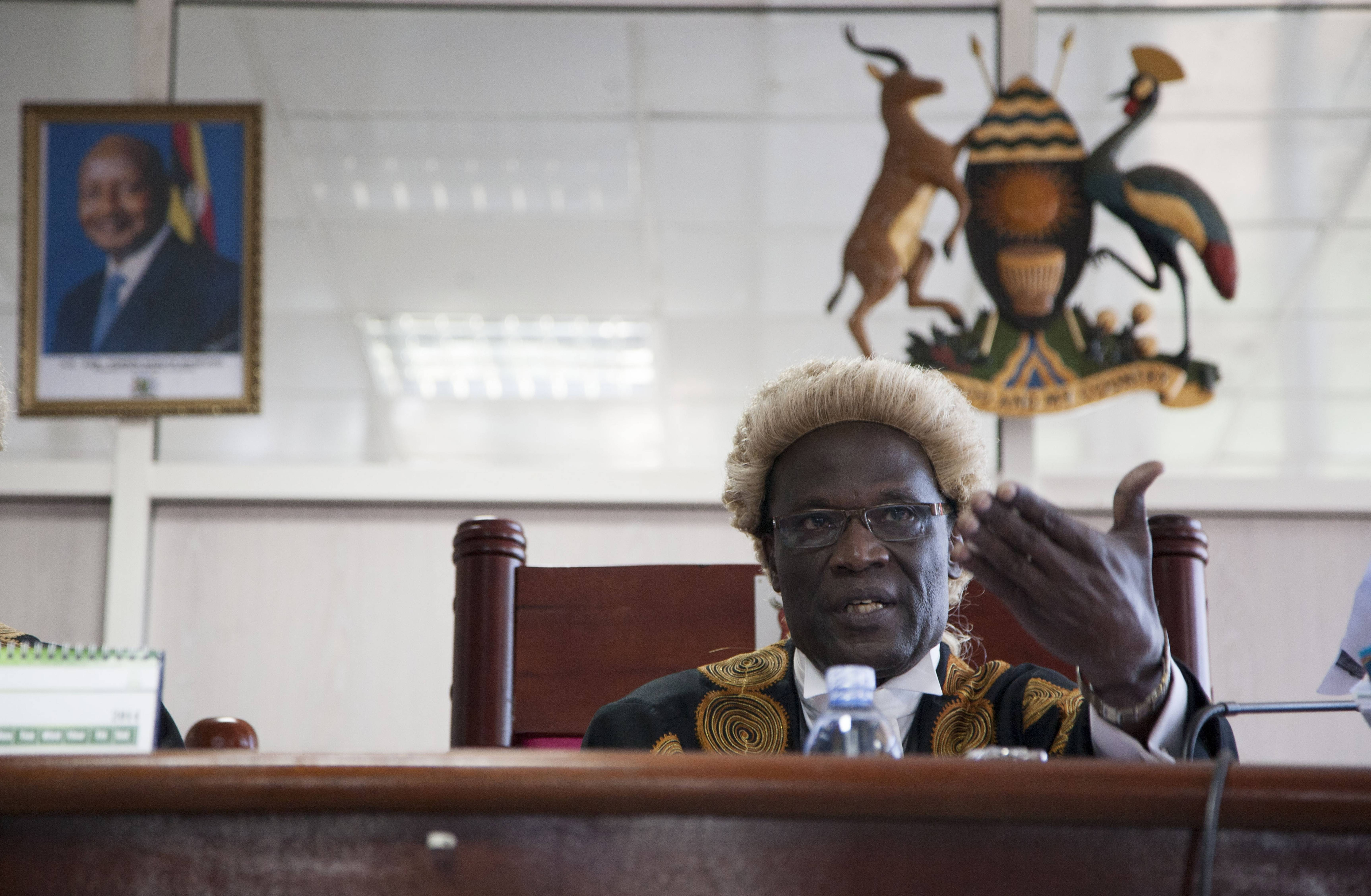 In this Aug. 1 photo, a picture of Uganda's president Yoweri Museveni hangs on the wall, left, as Judge Stephen Kavuma reads the verdict invalidating an anti-gay bill signed into law earlier this year, at the Constitutional court in Kampala, Uganda. When a Ugandan court overturned the country's Anti-Homosexuality Act this month, rights activists worldwide claimed a victory - but not gay Ugandans who fled persecution to live in a refugee camp in neighboring Kenya.