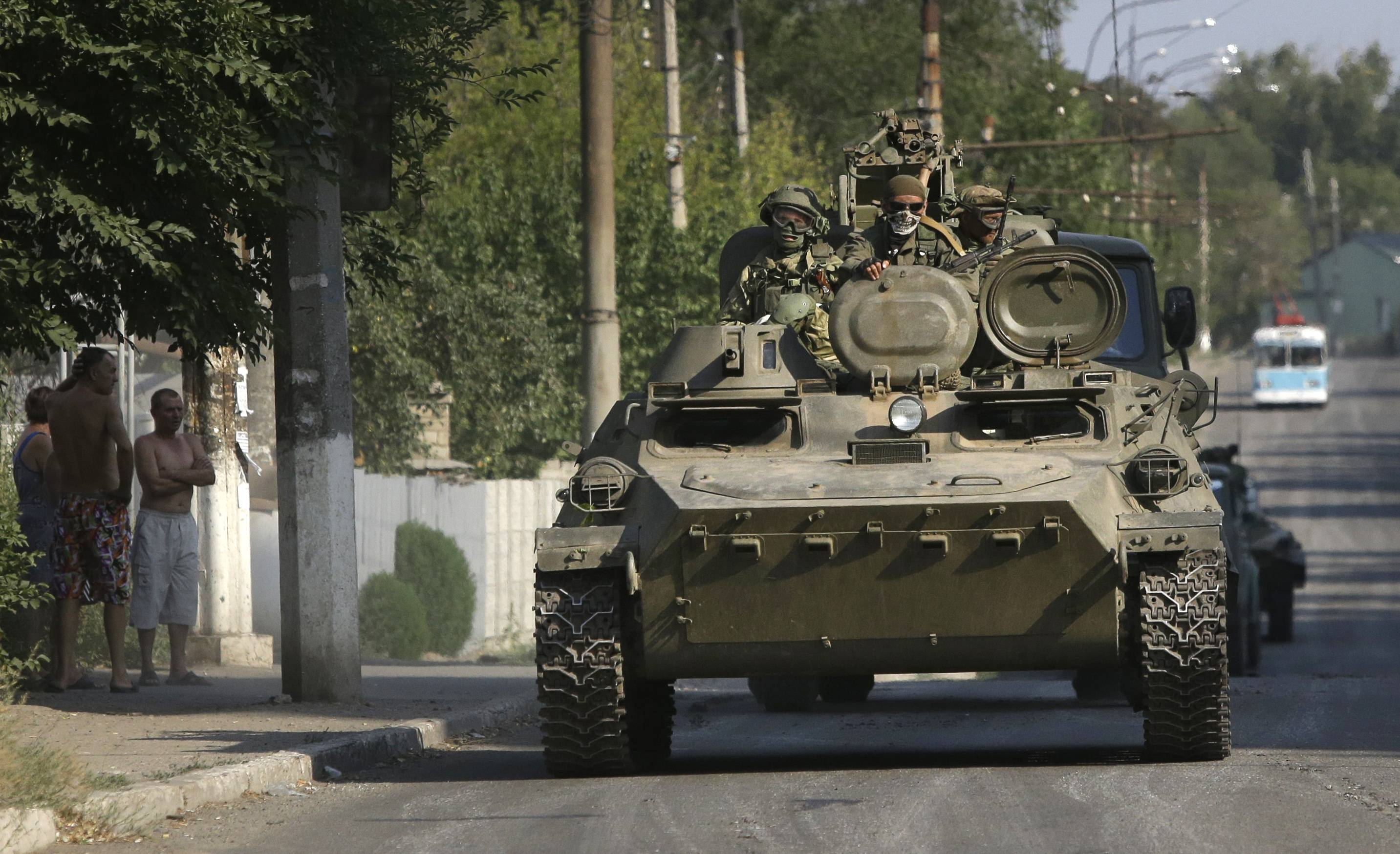 Pro-Russian rebels ride on an APC Sunday in the town of Krasnodon, eastern Ukraine. A column of several dozen heavy vehicles, including tanks and at least one rocket launcher, rolled through rebel-held territory on Sunday.
