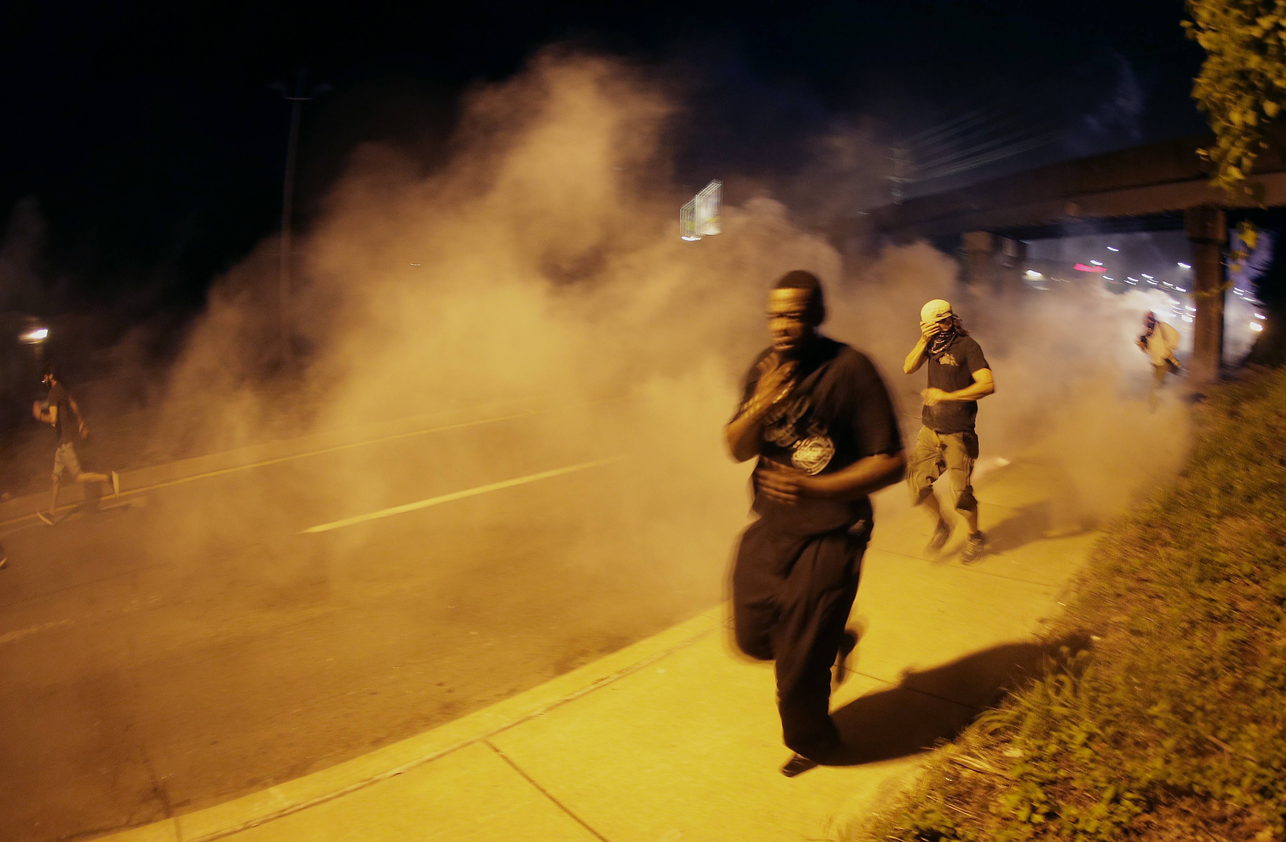 People run from tear gas after police dispersed a crowd Sunday, as they staged a protest for Michael Brown, who was killed by a police officer last Saturday in Ferguson, Mo. As night fell Sunday in Ferguson, another peaceful protest quickly deteriorated after marchers pushed toward one end of a street. Police attempted to push them back by firing tear gas and shouting over a bullhorn that the protest was no longer peaceful.