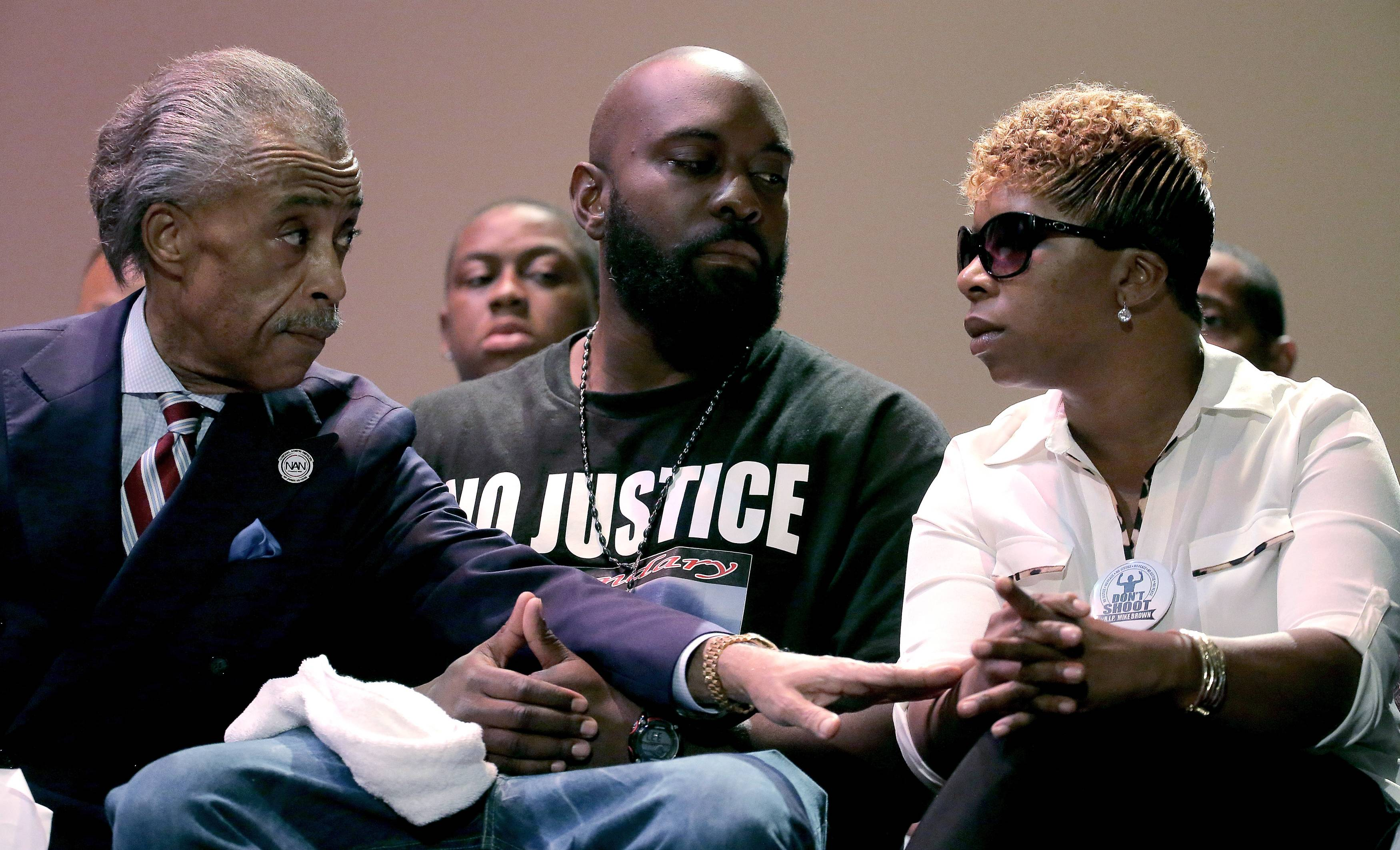 Rev. Al Sharpton speaks with parents of Michael Brown, Michael Brown Sr. and Lesley McSpadden during a rally Sunday at Greater Grace Church for their son who was killed by police last Saturday in Ferguson, Mo. Brown's shooting in the middle of a street, following a suspected robbery of a box of cigars from a nearby market, has sparked a week of protests, riots and looting in the St. Louis suburb.