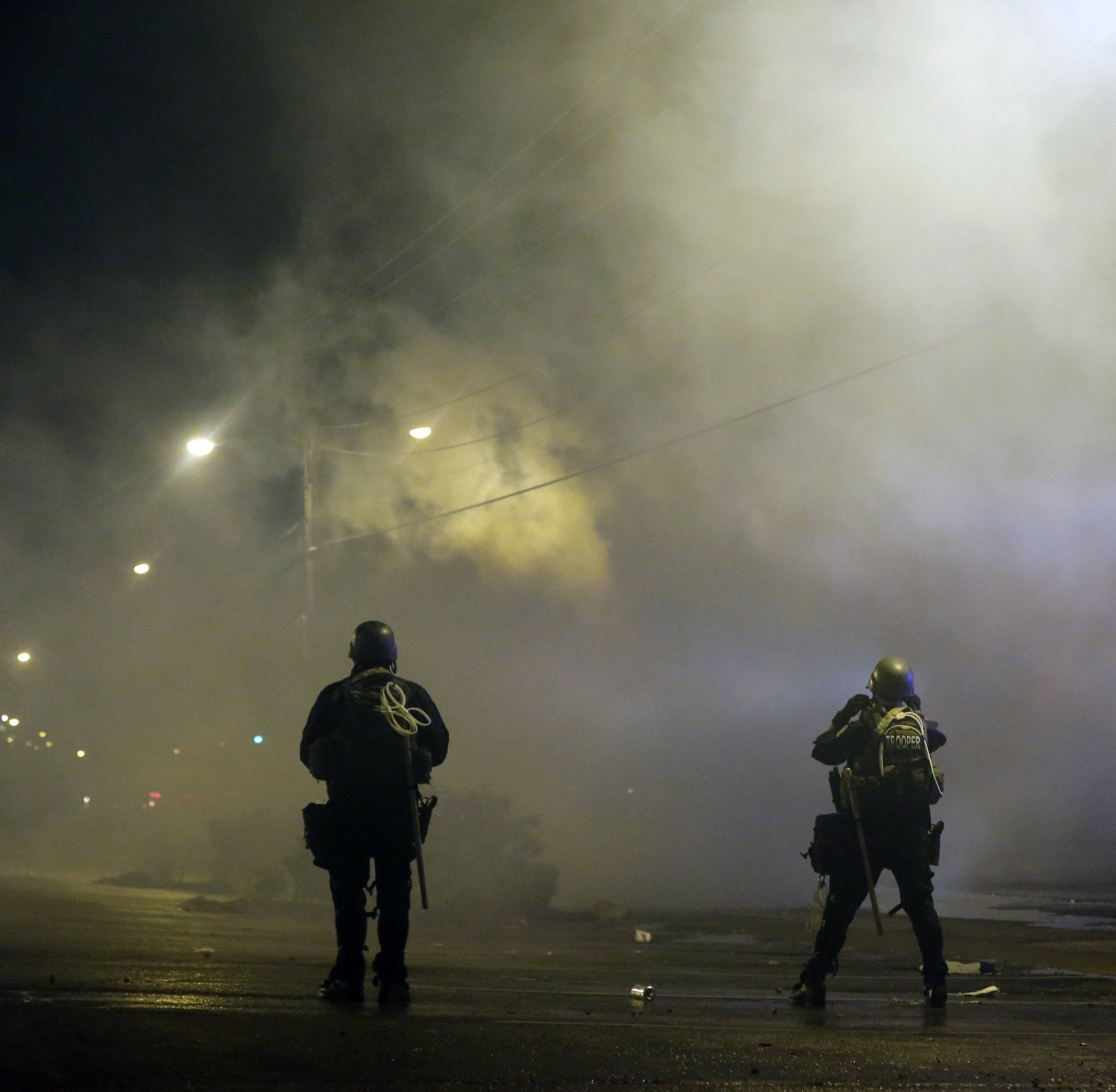 Tear gas was fired early Sunday morning to disperse a crowd protesting the shooting of teenager Michael Brown last Saturday in Ferguson, Mo.