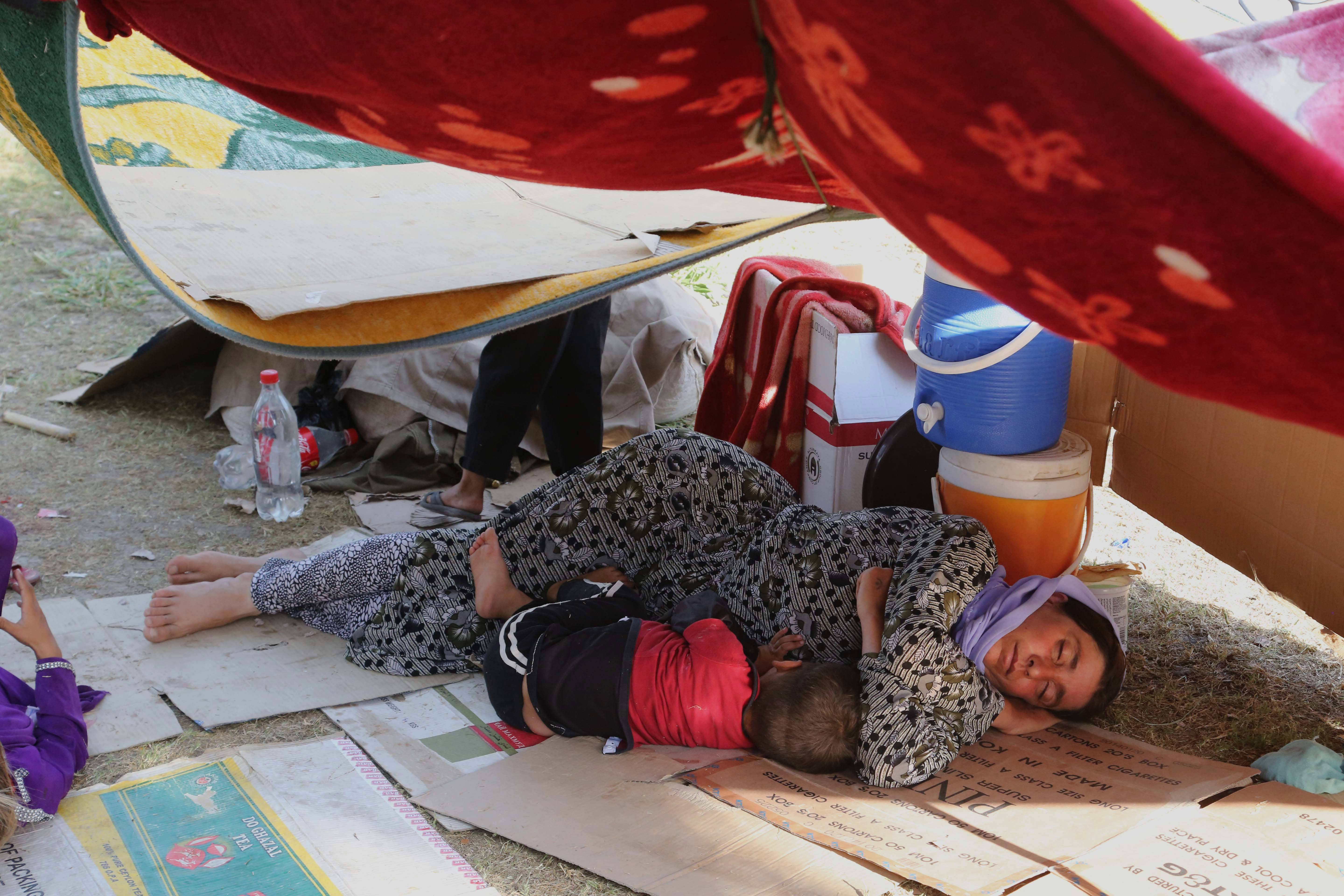 An Iraqi woman and her son from the Yazidi community sleep at a park near the Turkey-Iraq border at the Ibrahim al-Khalil crossing, as they try to cross to Turkey.