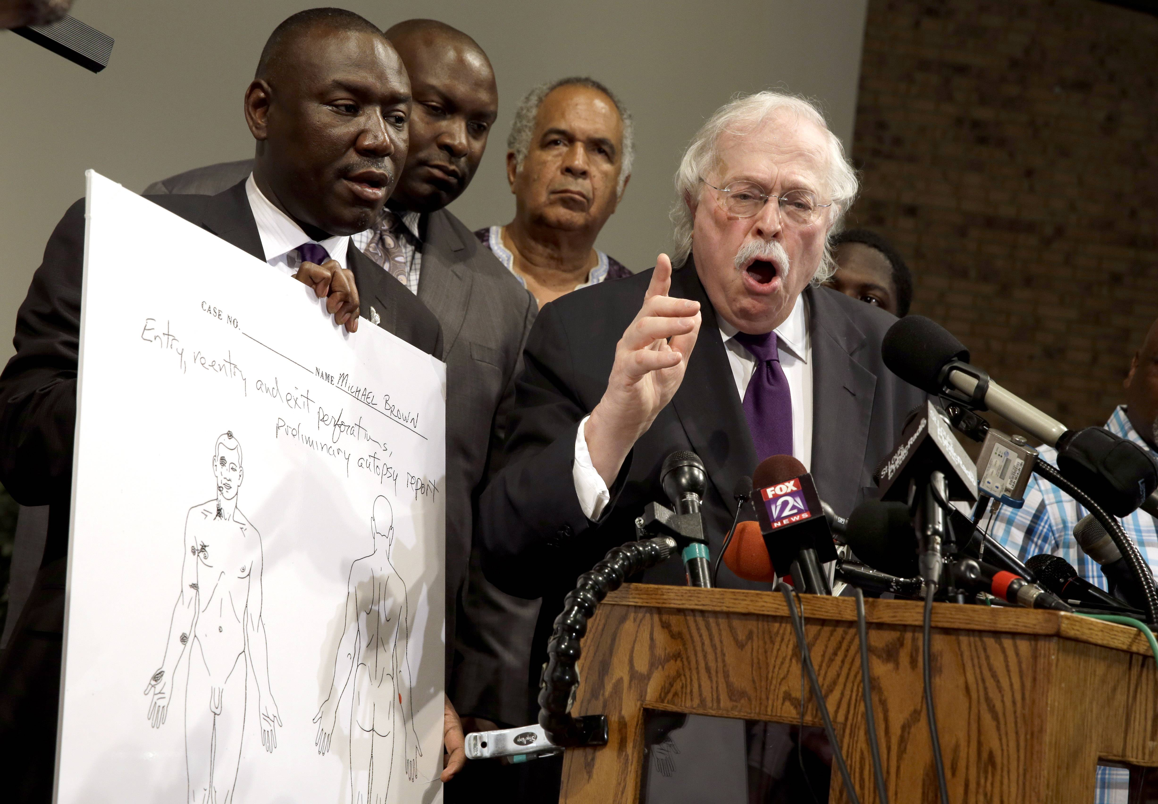 At left, Dr. Michael Baden speaks Monday as Brown family attorney Benjamin Crump holds a diagram produced during a second autopsy done on 18-year-old Michael Brown. At right, police tackle a man in Ferguson, Mo. Although there was no curfew Monday, police strictly enforced orders that protesters keep moving along the sidewalk.