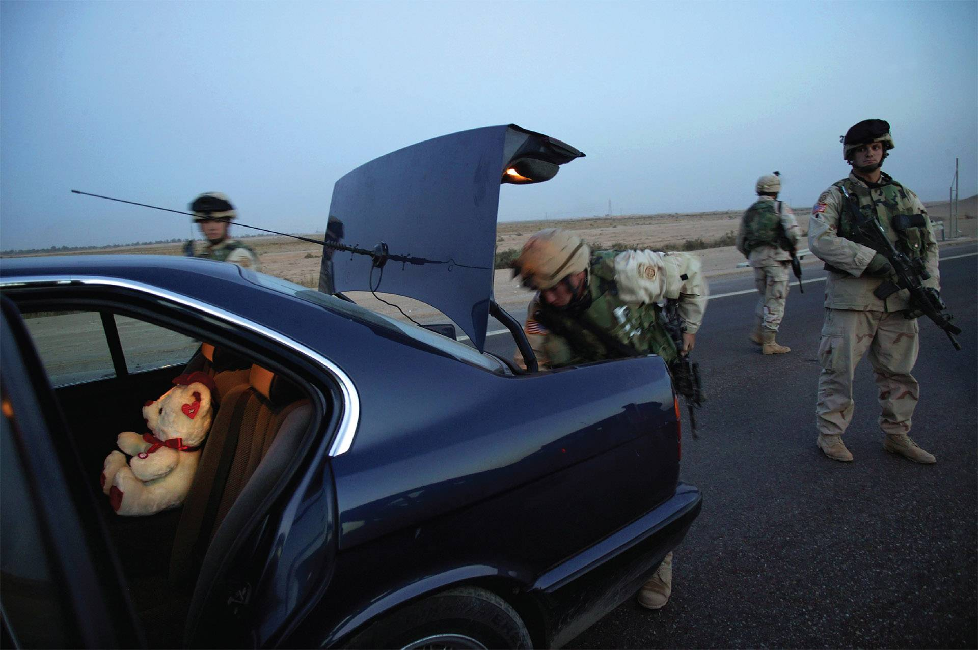 "In this photograph by Stephanie Sinclair, members of Charlie Company 1-505, 82nd Airborne Division, search a suspicious car during a mission to catch a loyalist of the late Iraqi dictator Saddam Hussein in Fallujah. It is part of an Elgin Community College exhibit, ""Collateral Damage: The Human Faces of War,"" featuring the work of four award-winning documentary photographers depicting the personal cost of war."