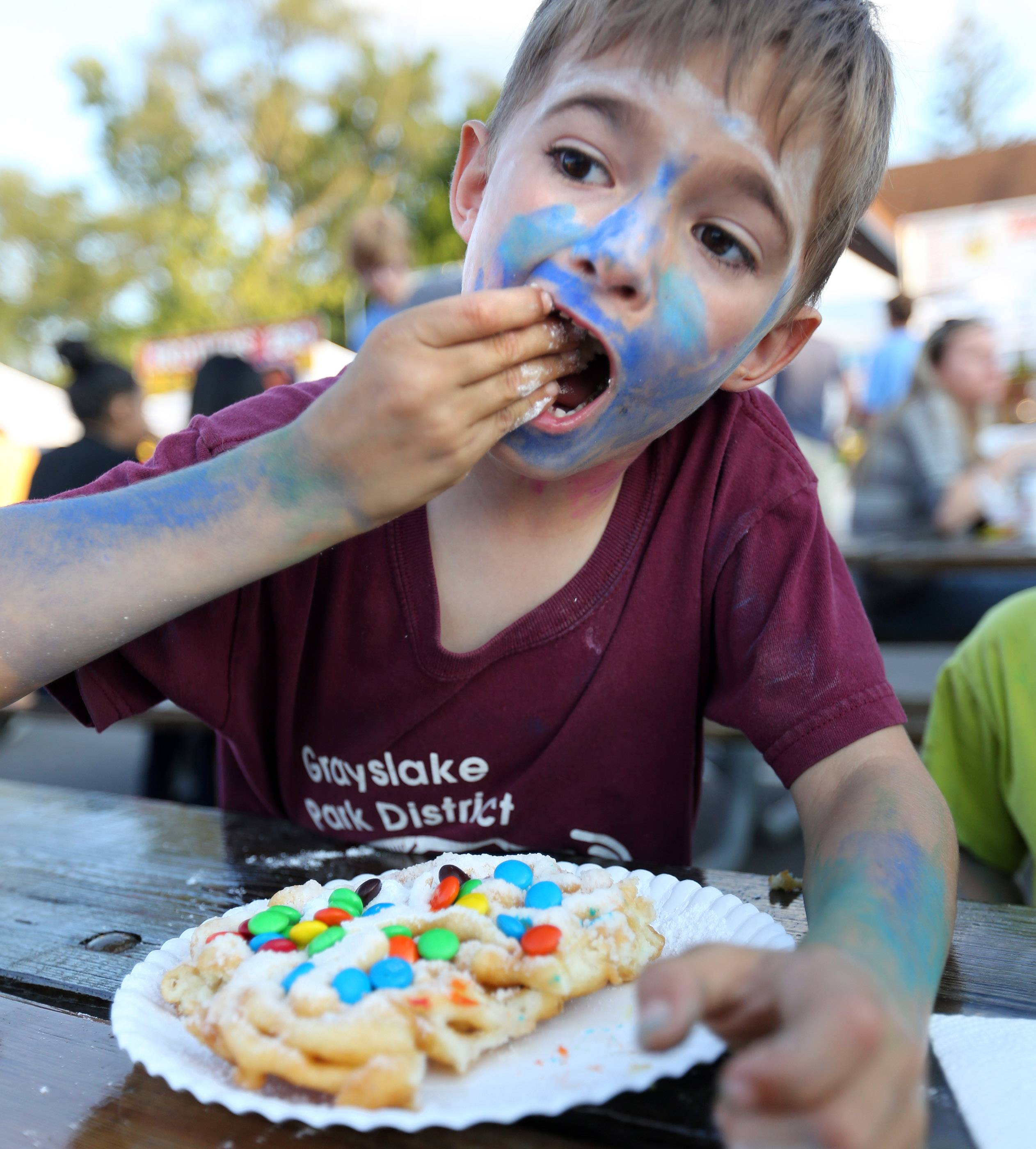Joey Pavlik, 3, of Grayslake, said the best food item at the first day of Grayslake Summer Days festival is the M&M funnel cake.