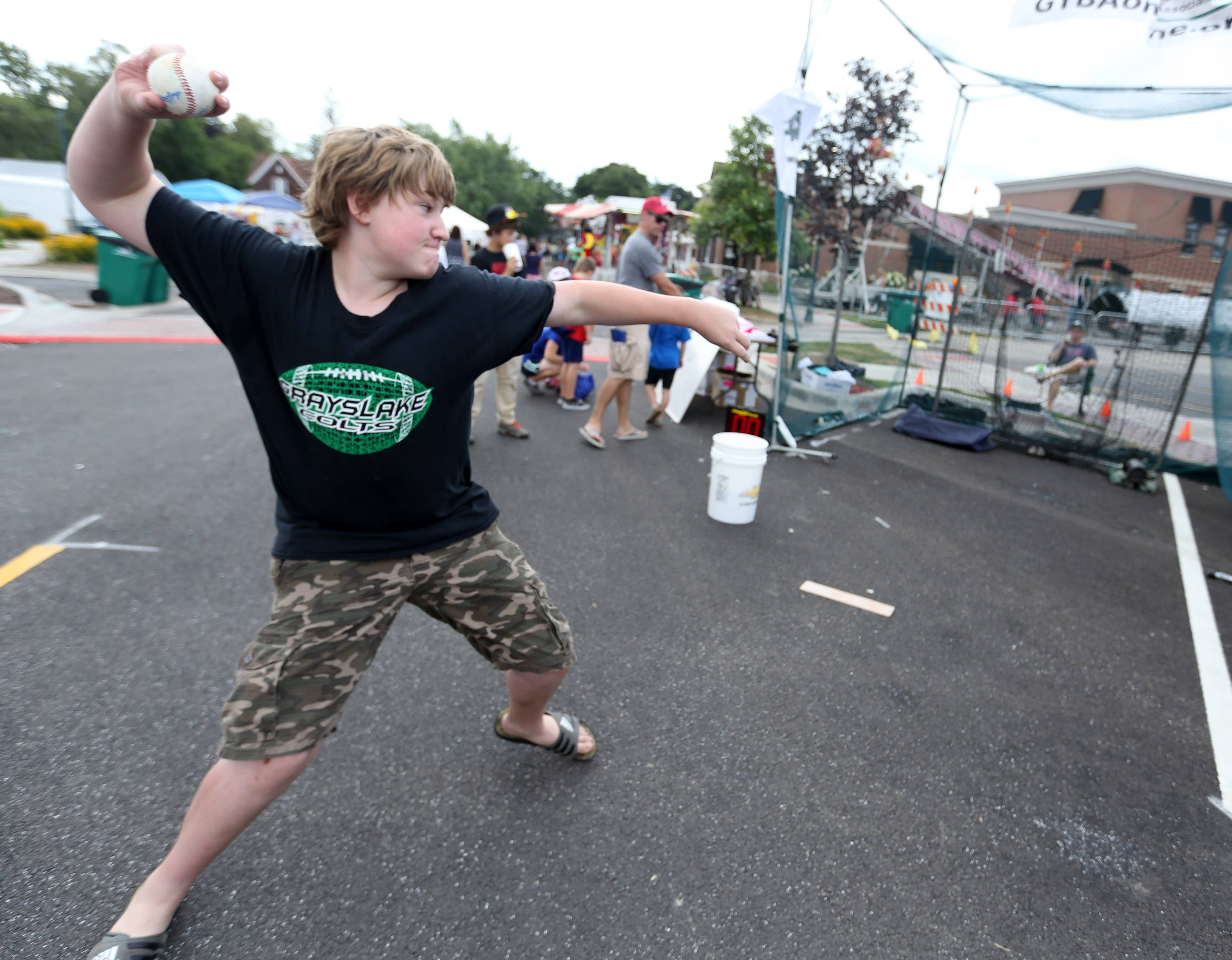 Tristan Gottstein, 13, of Grayslake, throws a 54 mph pitch at Grayslake Youth Baseball Association's pitching booth on Saturday at the second day of Grayslake Summer Days festival in downtown.