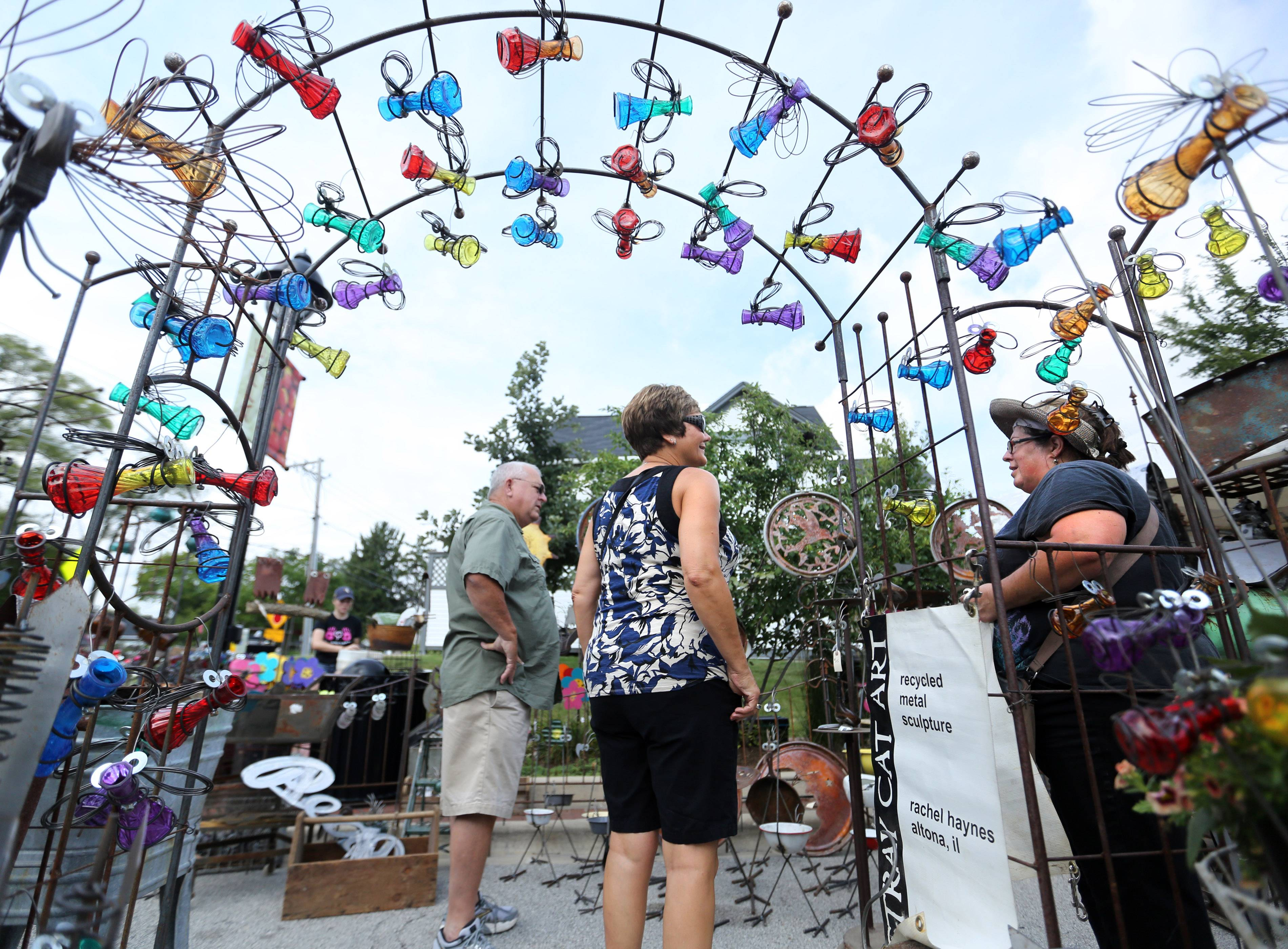Linda and Mike Mouser, of Carlock, Illinois, talk with metal and glass artist Rachel Haynes of Altona, Illinois, about her large display of work at Long Grove Village Art Market on Saturday in Long Grove.