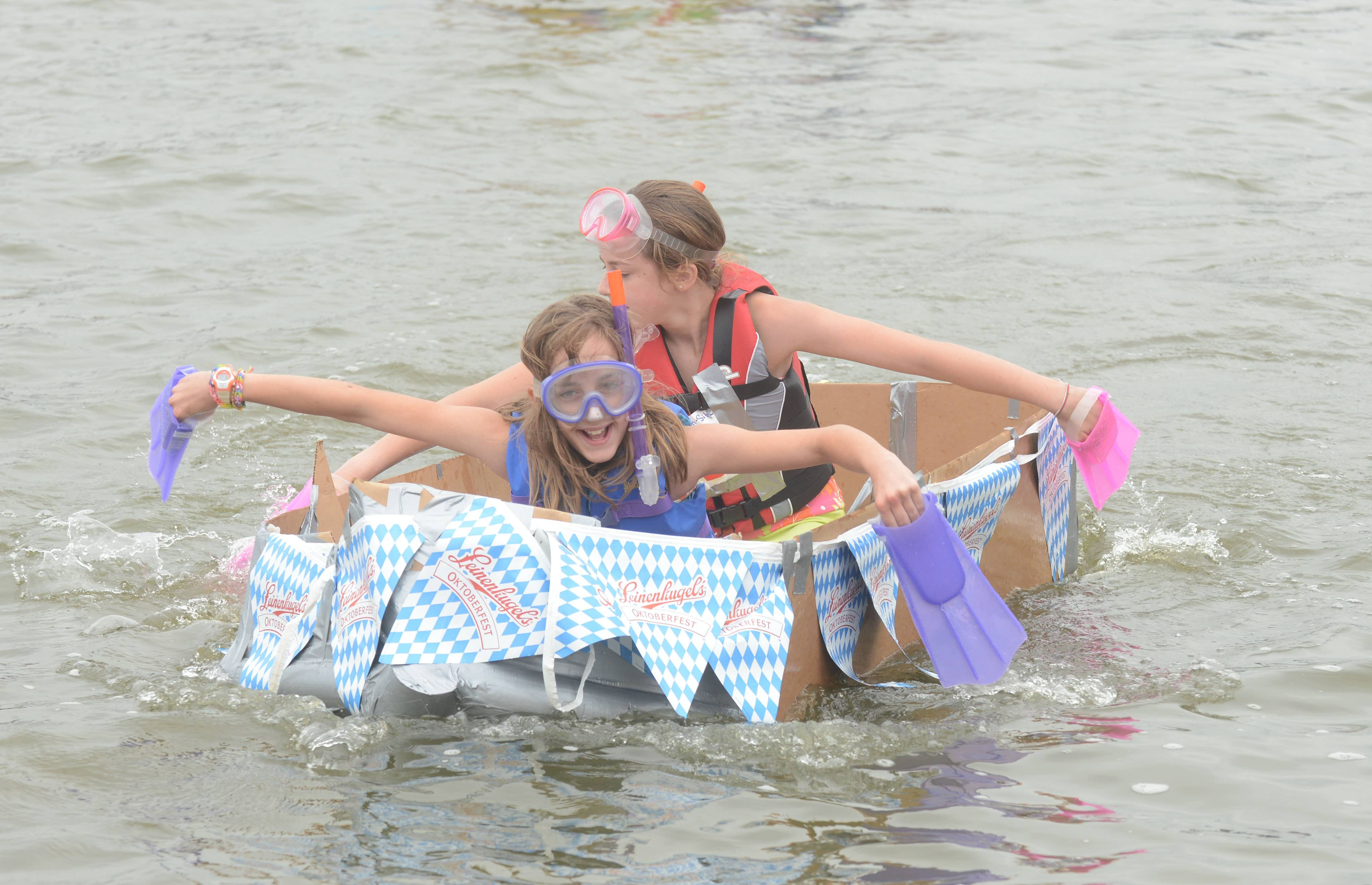 Olivia and Grace Camel, of Barrington, give it their all during the Fox Lake's 17th annual Cardboard Boat races at Lake Front Park in Fox Lake Saturday.