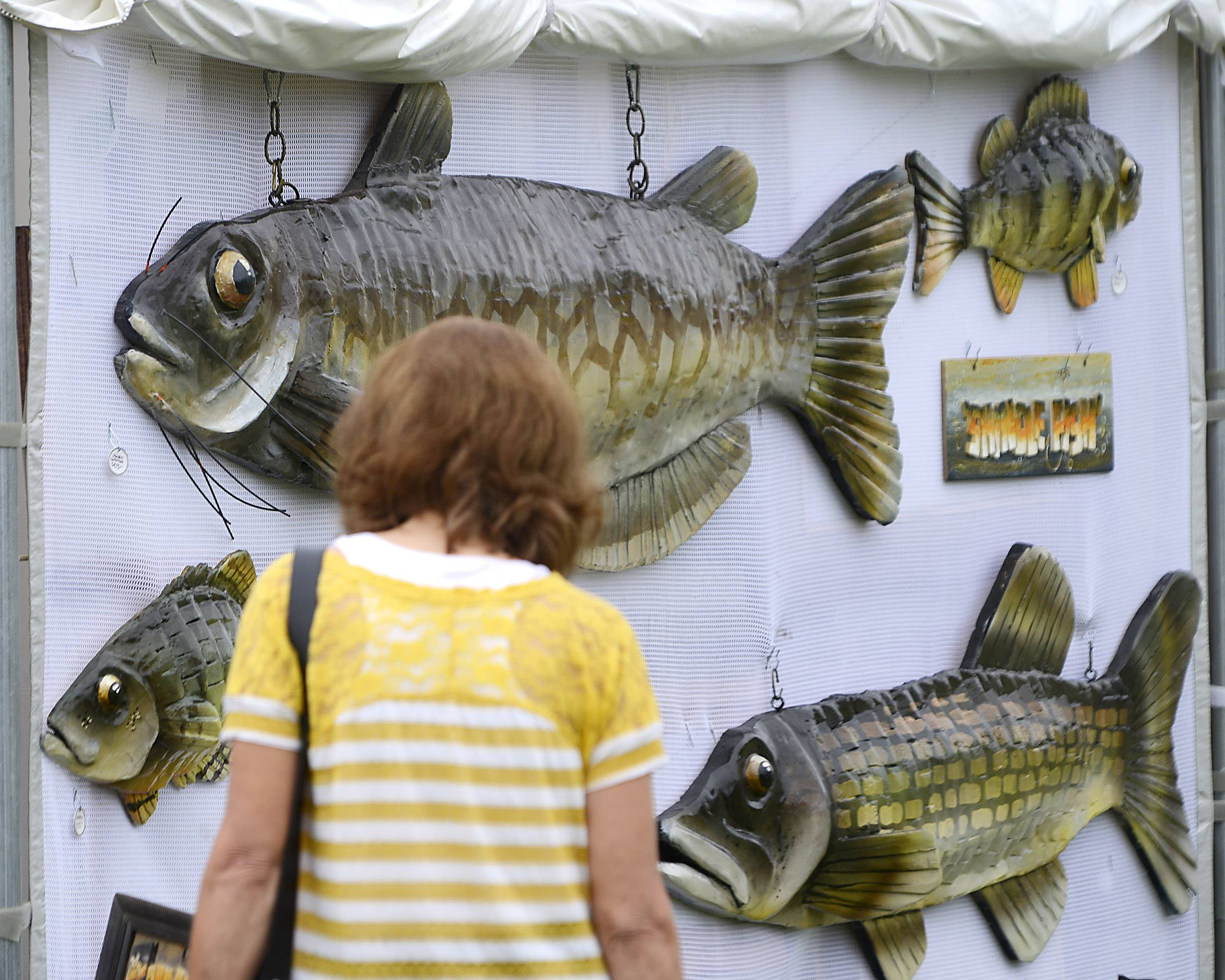 "Several ""Shingle Fish,"" large hand-crafted wooden fish painted by Wheaton artist Dick Dahlstrom, wait Sunday at the Huntley ArtFest as visitors pass on Main Street. More than 40 artists from the Midwest displayed their work."
