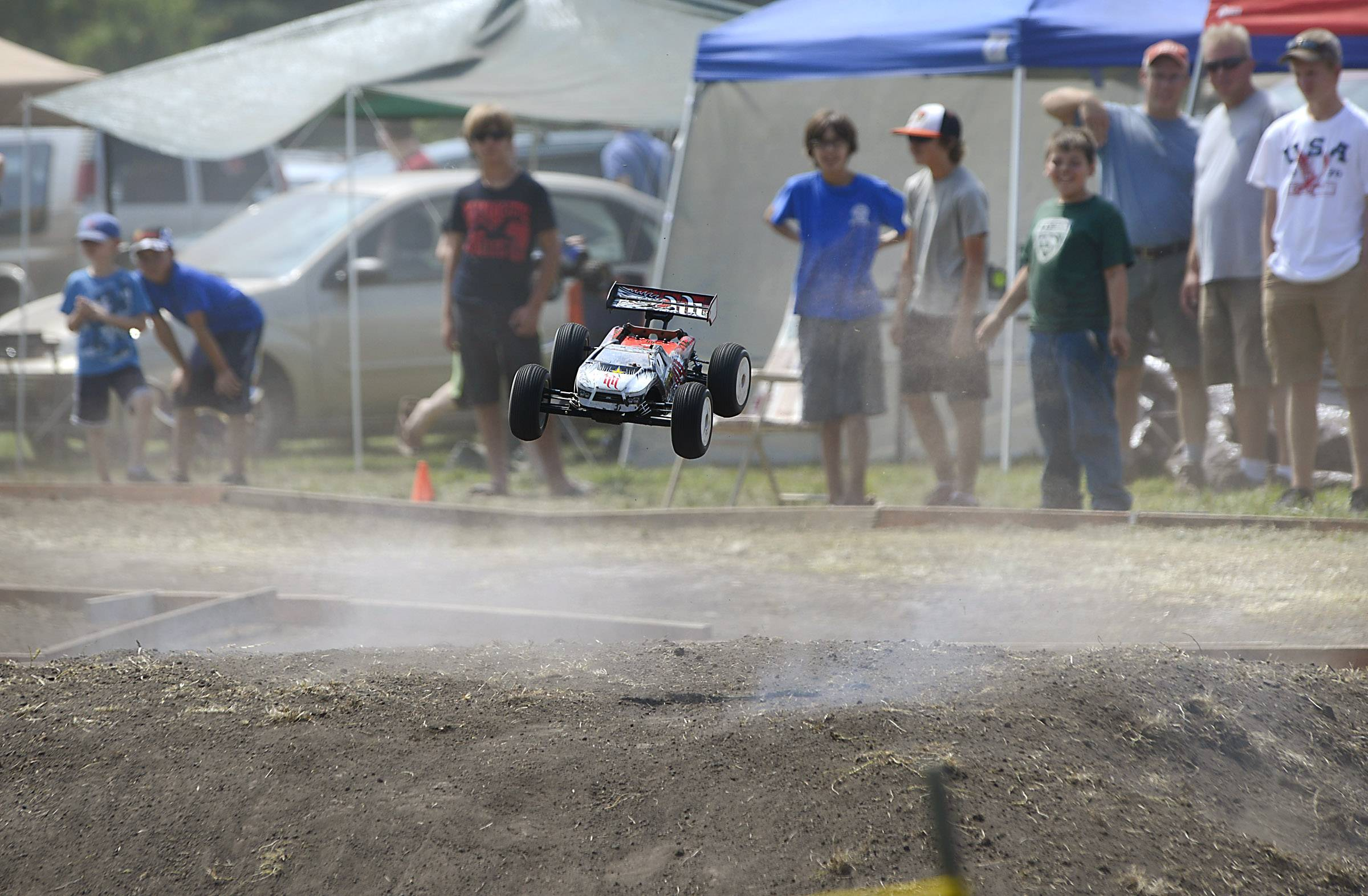 An RC car flies over a jump on the dirt track Sunday at the Elburn Days festival in Lions Park on Route 47. Competitors race in age groups and against similar cars and trucks. The racing counted toward points earned for trophies and prizes at the end of the season, from Hobby Town USA in St. Charles.