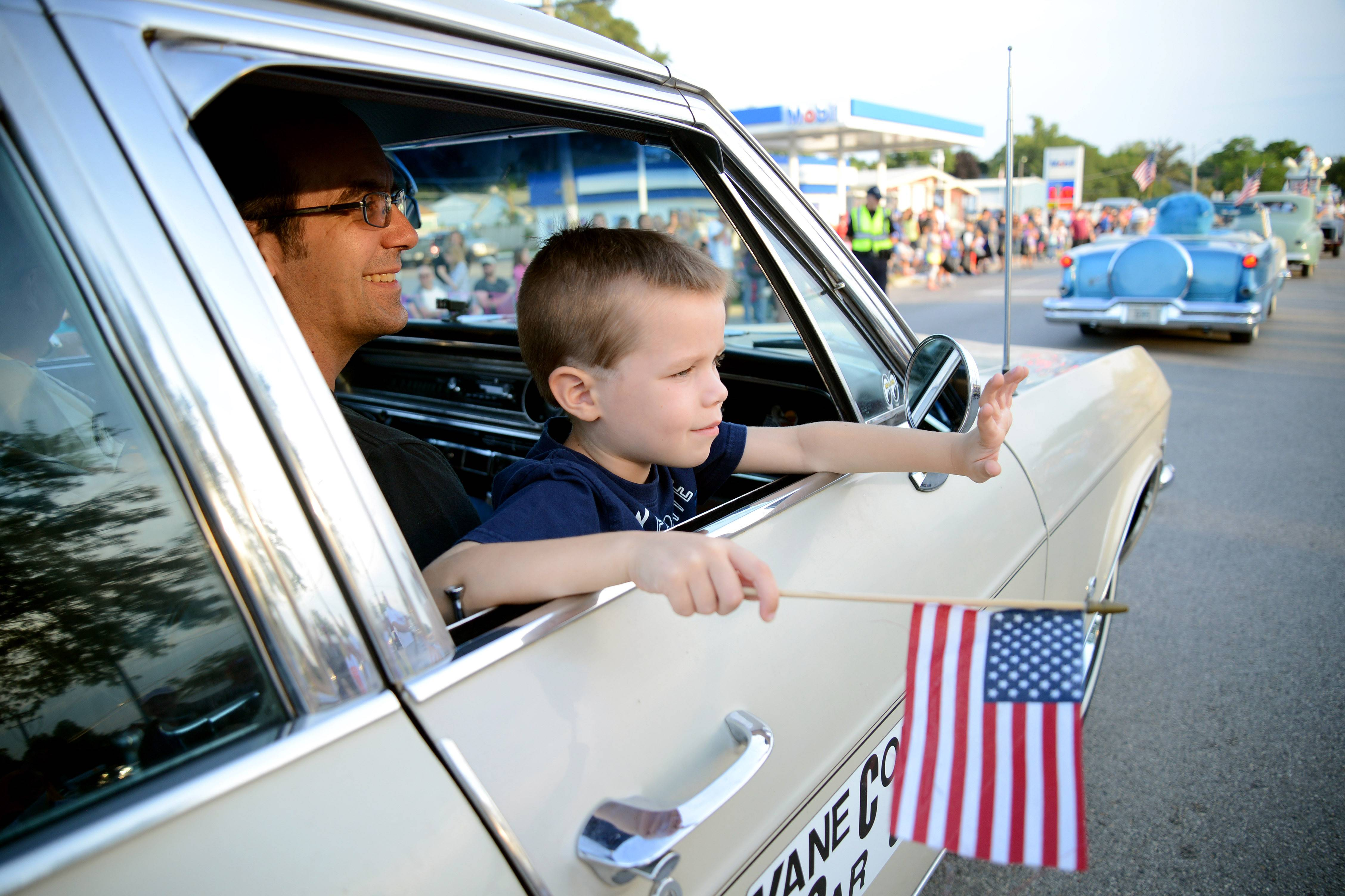Ruben Pittman, 5, of Sycamore, waves to the crowd at the Elburn Days parade while seated in his dad Rick's lap and riding in the '65 Chevy Impala driven by his grandfather, Ronn Pittman of Batavia, on Friday.