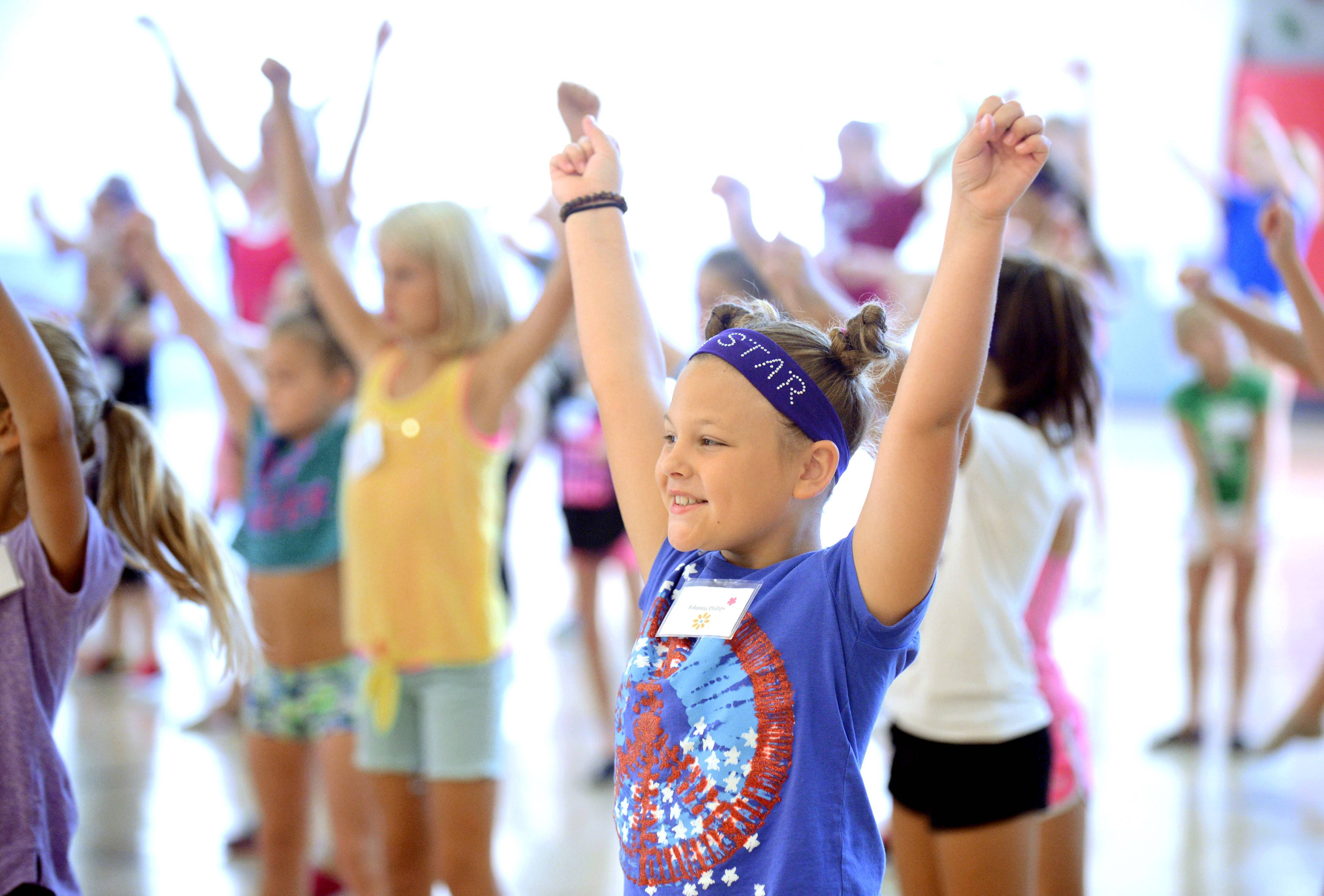 Johanna Phillips, 8, of St. Charles practices the cheer to the school song for St. Charles North High School at the drill and dance teams' 15th annual dance clinic for elementary and middle school students at Bell-Graham Elementary School in St. Charles.