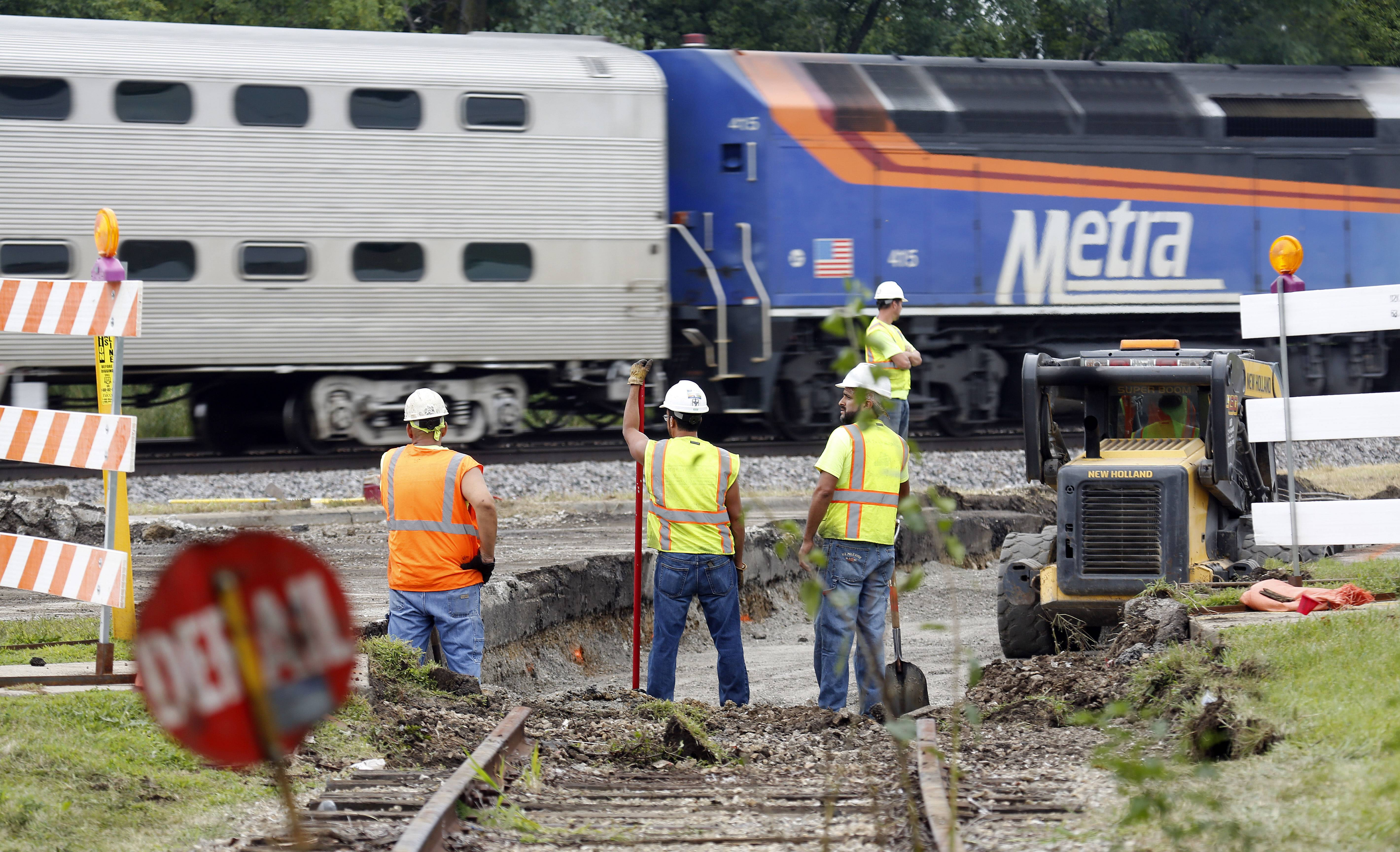 A Metra train travels west along Big Timber Road Tuesday as repair work on the railroad track spur at 1600 Big Timber Road continues. Big Timber Road is closed from Todd Farm Drive to McLean Boulevard through at least Friday.