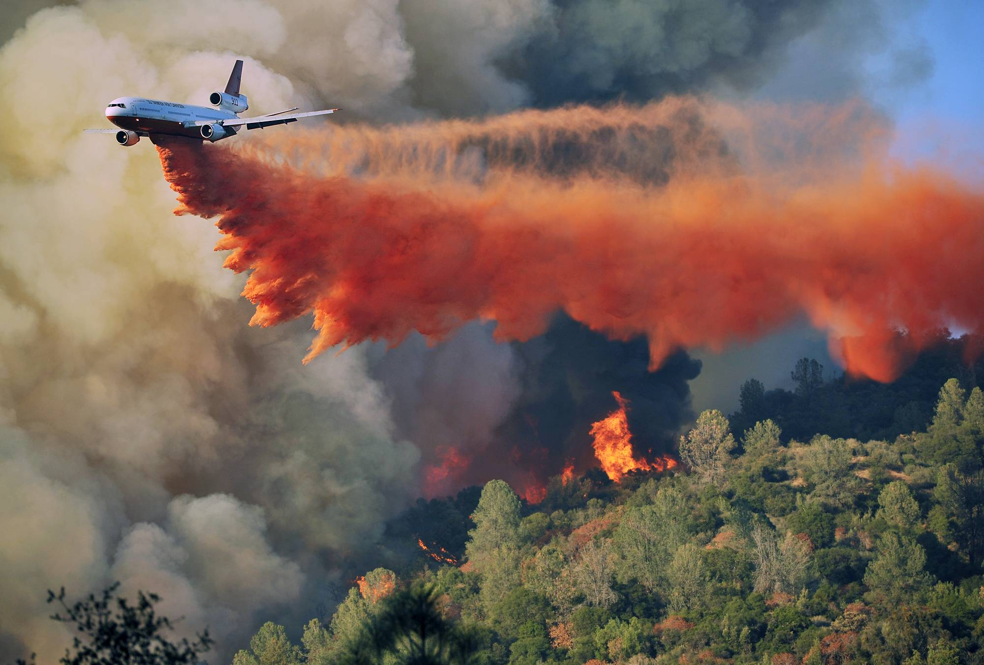 An air tanker drops fire retardent on a fire which was burning on a ridge northeast of Oakhurst, Calif., Monday. One of several wildfires burning across California prompted the evacuation of hundreds of people in a central California foothill community near Yosemite National Park, authorities said.