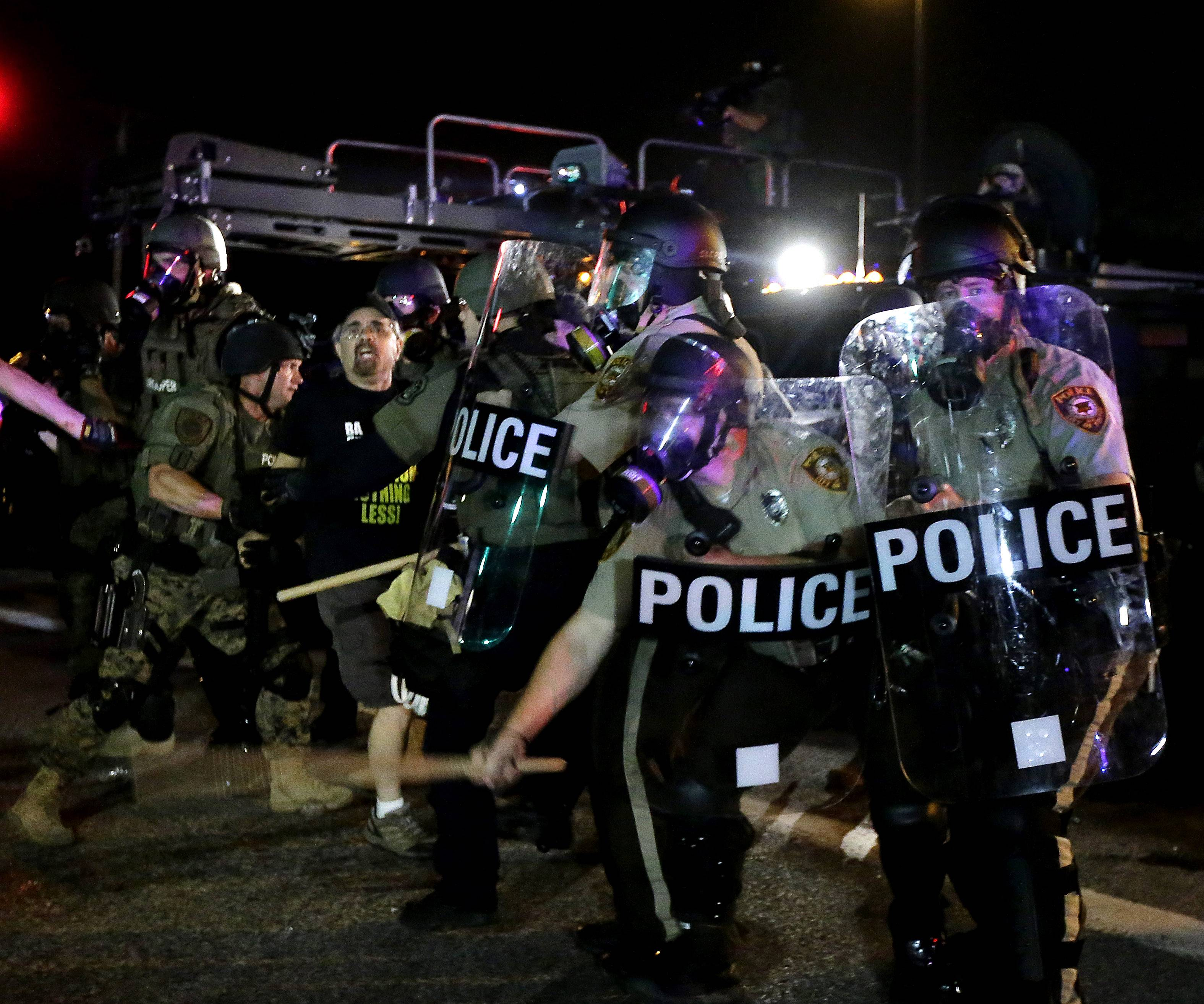 A man is detained after a standoff with police Monday, Aug. 18, 2014, during a protest for Michael Brown, who was killed by a police officer Aug. 9 in Ferguson, Mo. Brown's shooting has sparked more than a week of protests, riots and looting in the St. Louis suburb.