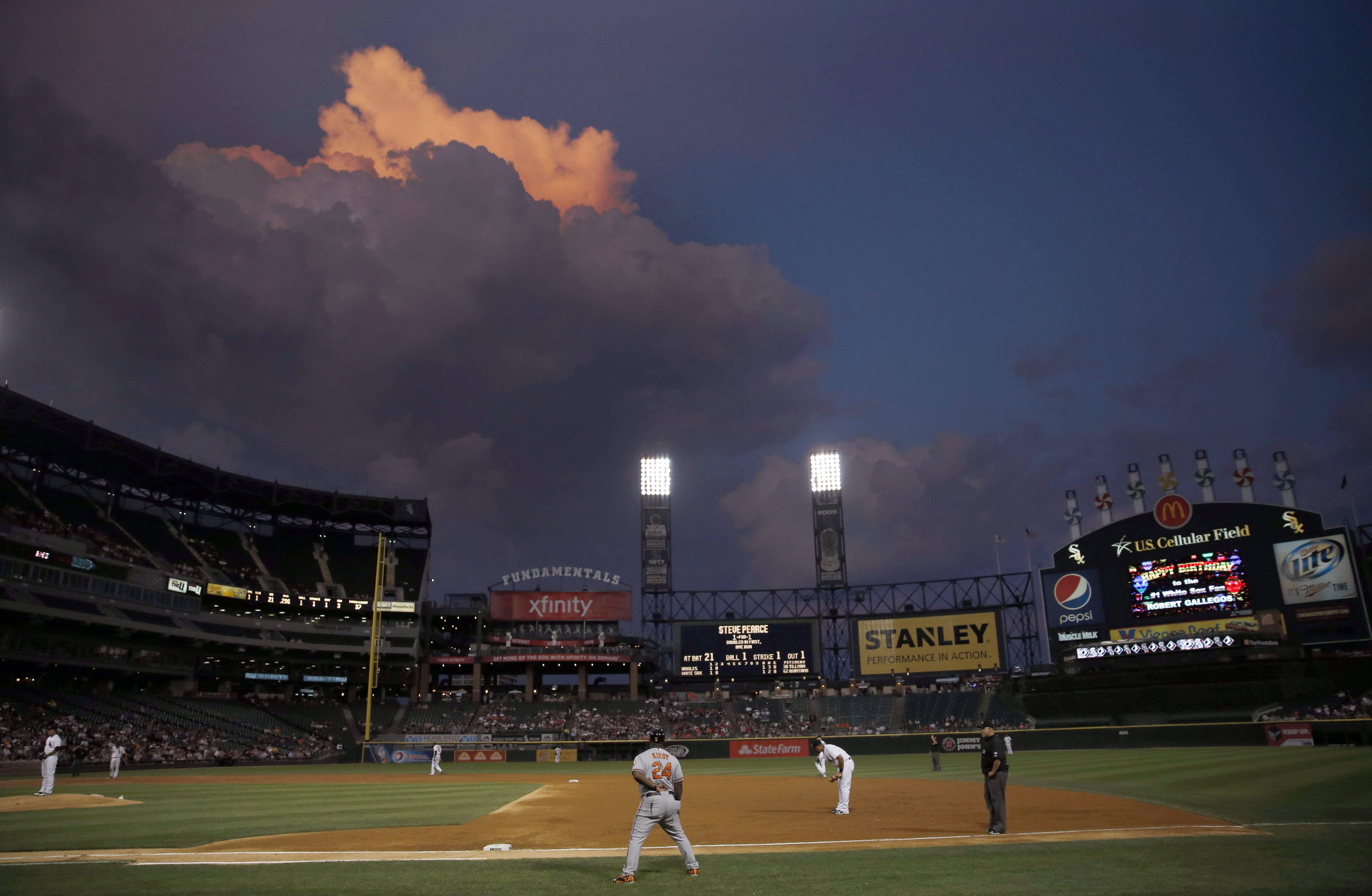 The setting sun lights up storm clouds as they drift over Lake Michigan near U.S. Cellular Field during the third inning of a baseball game between the Chicago White Sox and the Baltimore Orioles, Tuesday, Aug. 19, 2014, in Chicago. (AP Photo/Charles Rex Arbogast)