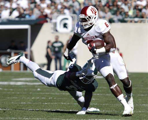 Indiana's Tevin Coleman (6) avoids a tackle by Michigan State's Darian Hicks during the first quarter of an NCAA college football game, Saturday, Oct. 12, 2013, in East Lansing, Mich. Michigan State won 42-28. (AP Photo/Al Goldis)