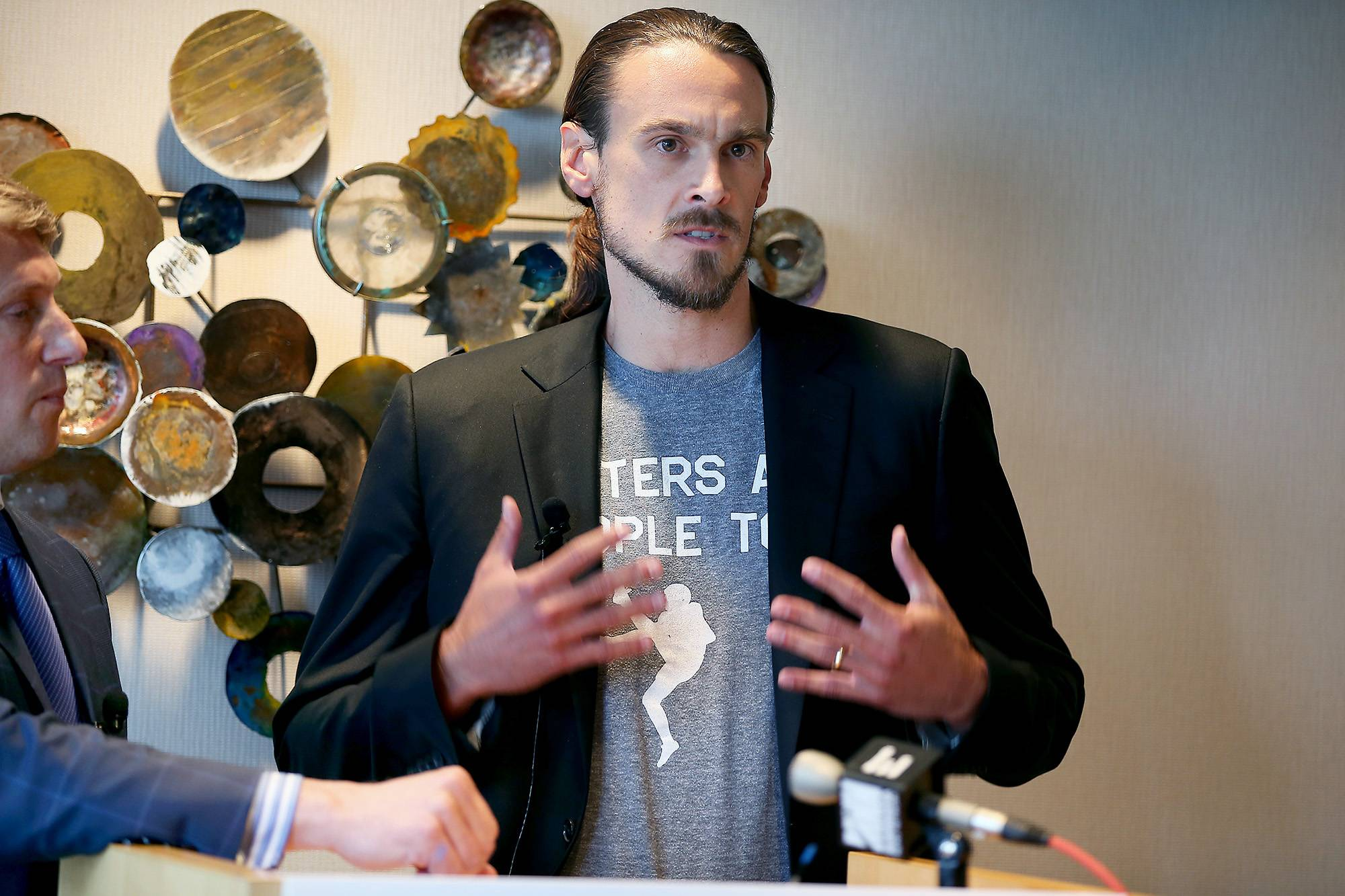Former Minnesota Vikings punter Chris Kluwe, right, says he's reached a settlement with the team to avert a threatened lawsuit over his release. Kluwe had accused the Vikings of cutting him over his activism on gay rights issues.