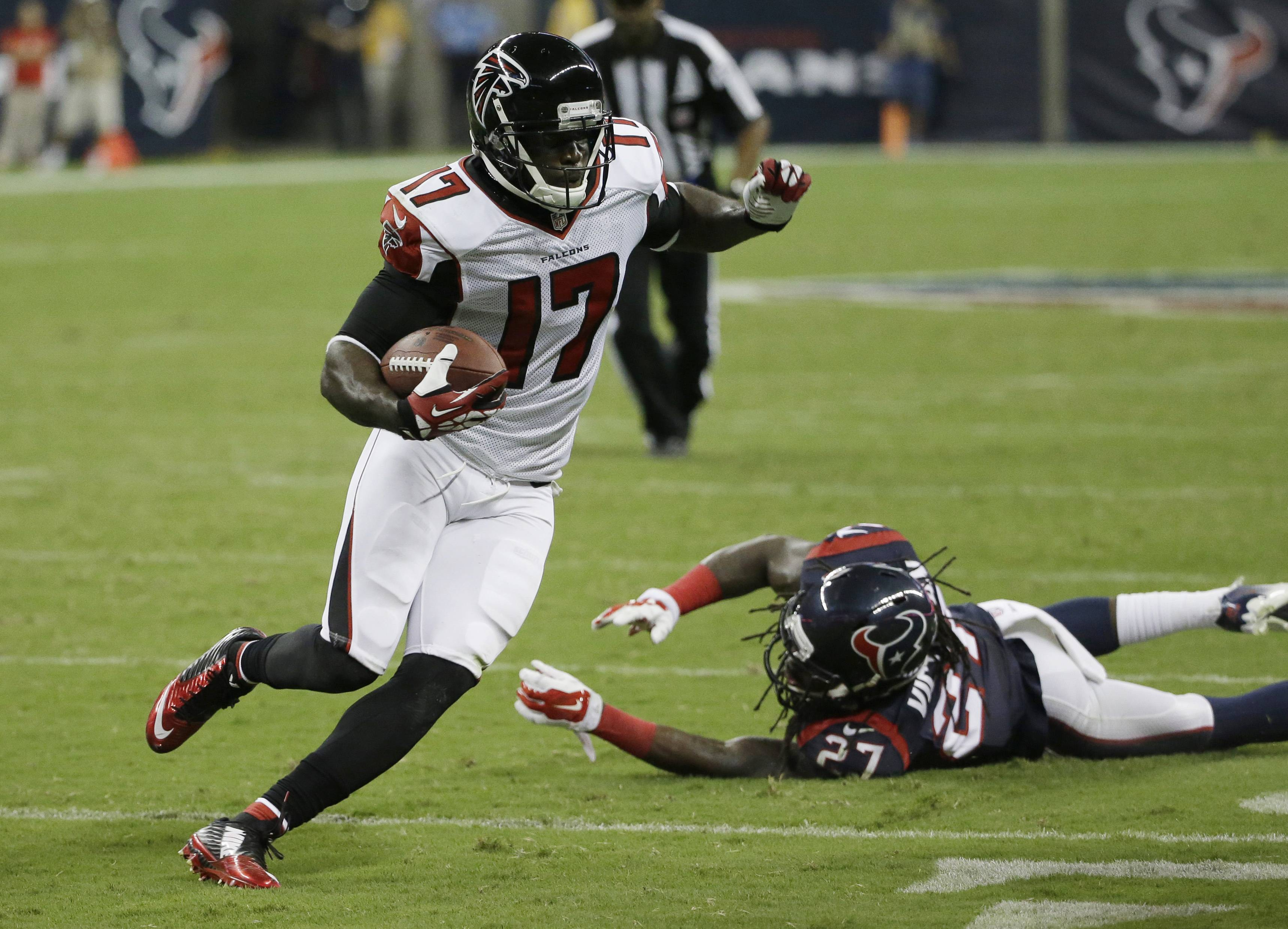 Atlanta Falcons returner Devin Hester (17) evades Houston's Josh Victorian (27) as he runs for a touchdown Saturday in Houston.