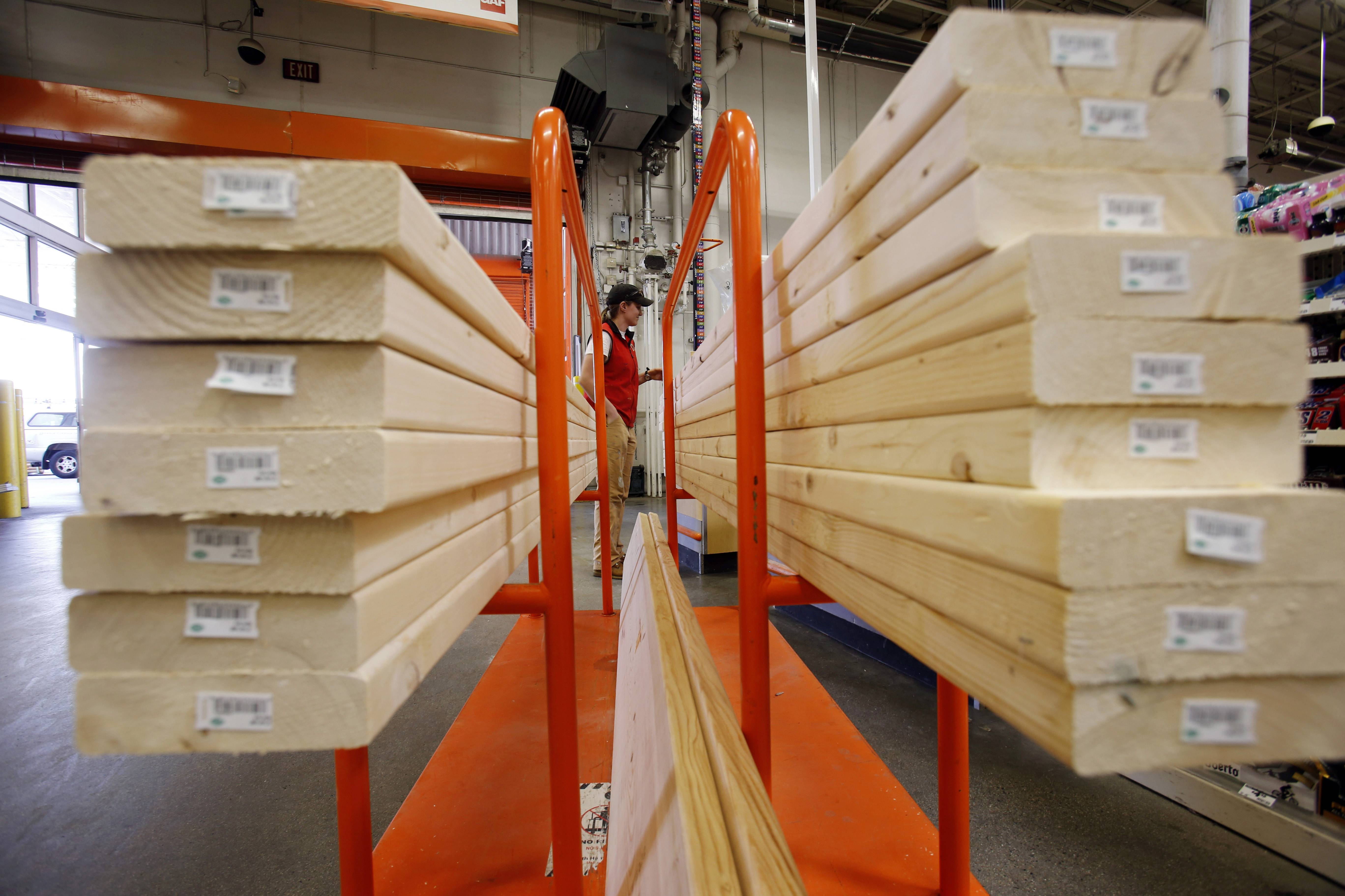 A shopper checks out with her lumber at a Home Depot in BostonHome Depot Inc., the largest U.S. home-improvement retailer, posted second-quarter profit that topped analysts' estimates and raised its forecast for the year as sales of seasonal merchandise rebounded. The shares gained.