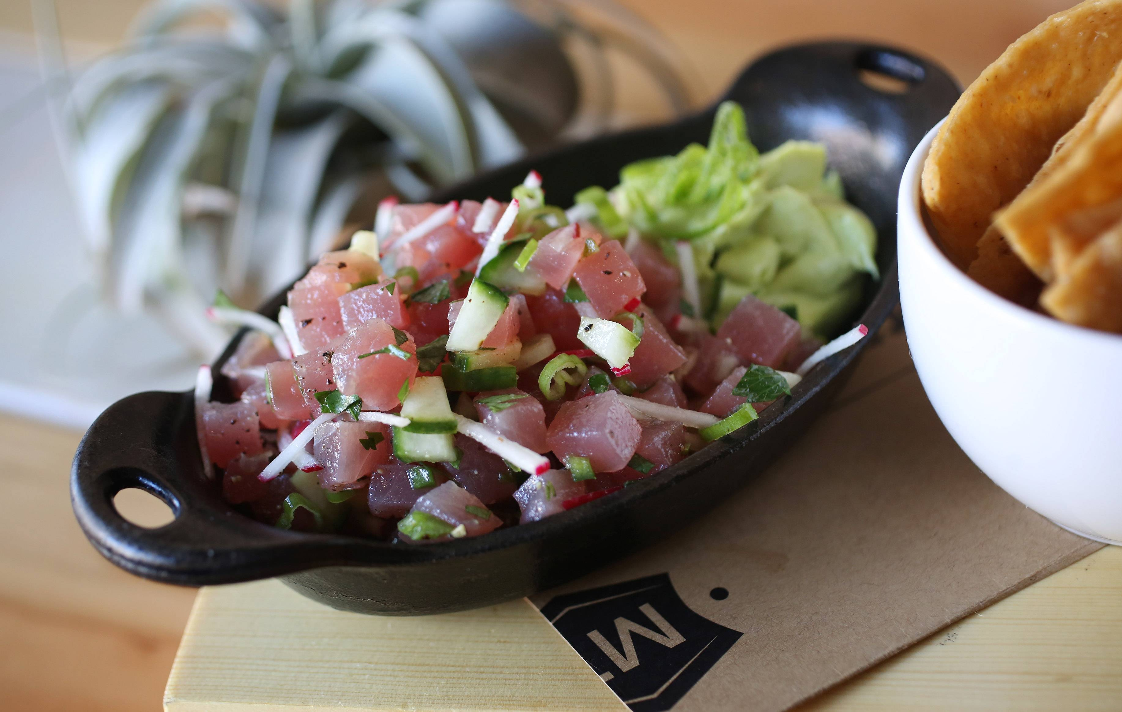 Chef Lee Kuebler serves tuna tartare with homemade tortilla chips at Milwalky Trace in Libertyville.