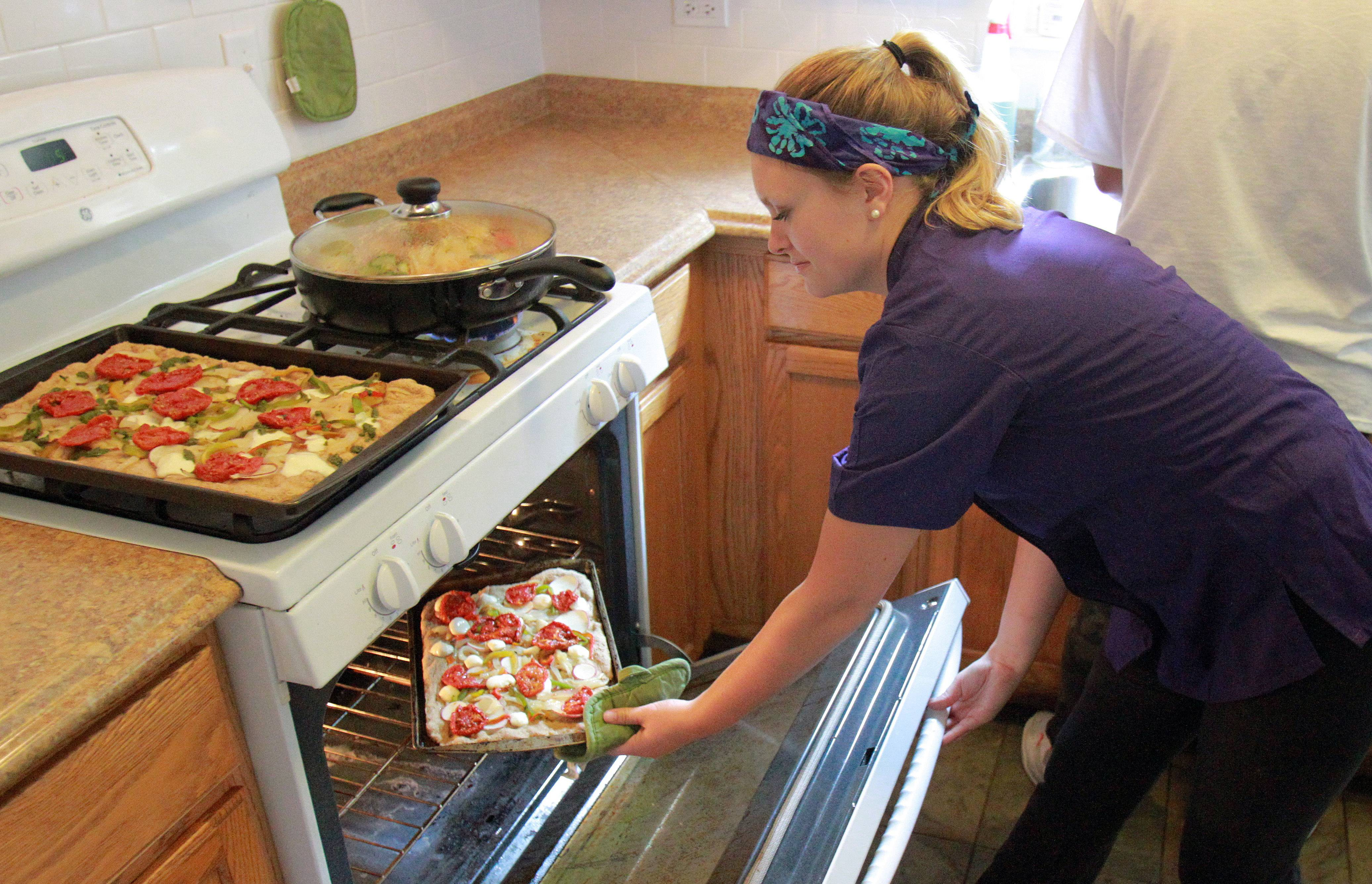 MacKenzie Le Beau, 21, an intern at Prairie Farm Corps at Prairie Crossing in Grayslake, puts a flat bread pizza into the oven. The pizza is topped with ingredients from the local farm.
