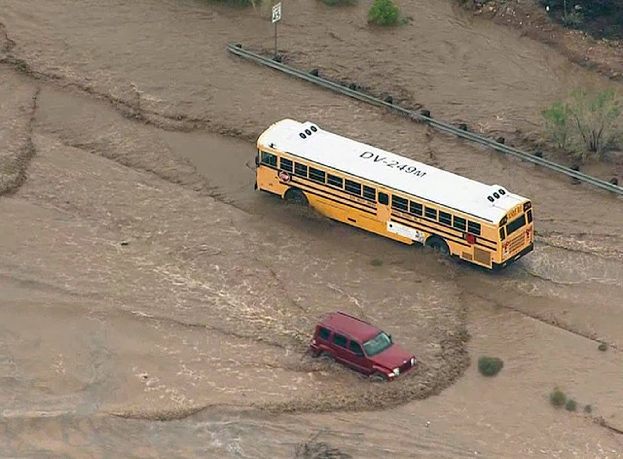 A school bus navigates a flooded road north of Phoenix Tuesday. It was not known if there were children aboard the bus at the time. The area was flooded after several inches of rain pummeled the state.
