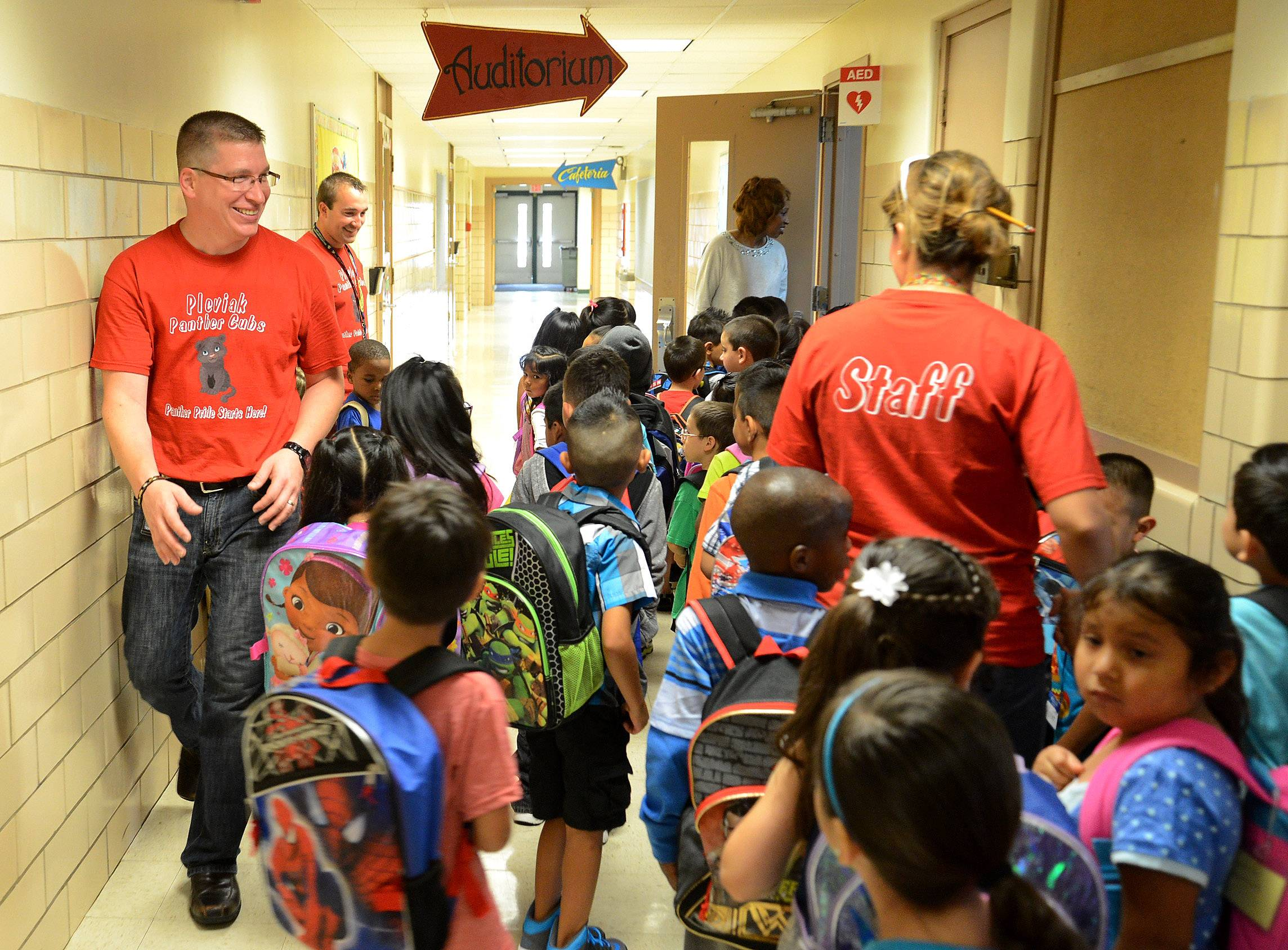 Pleviak Elementary School Principal Nick Heckel, left, directs children on the first day of classes for Round Lake Area Unit District 116's new kindergarten at the building in Lake Villa.