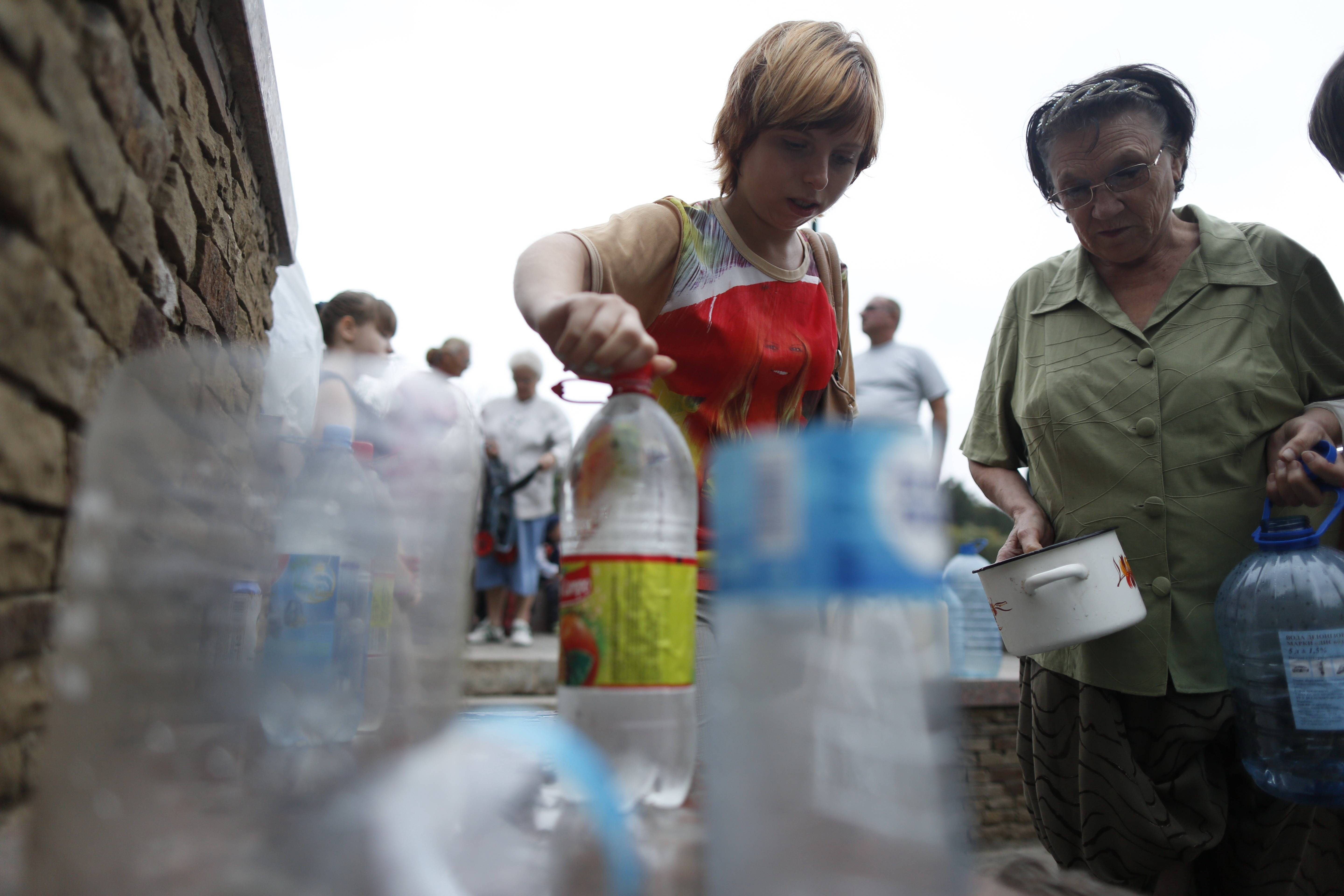 Local citizens line up to collect water on a street in Donetsk, Ukraine, Monday.