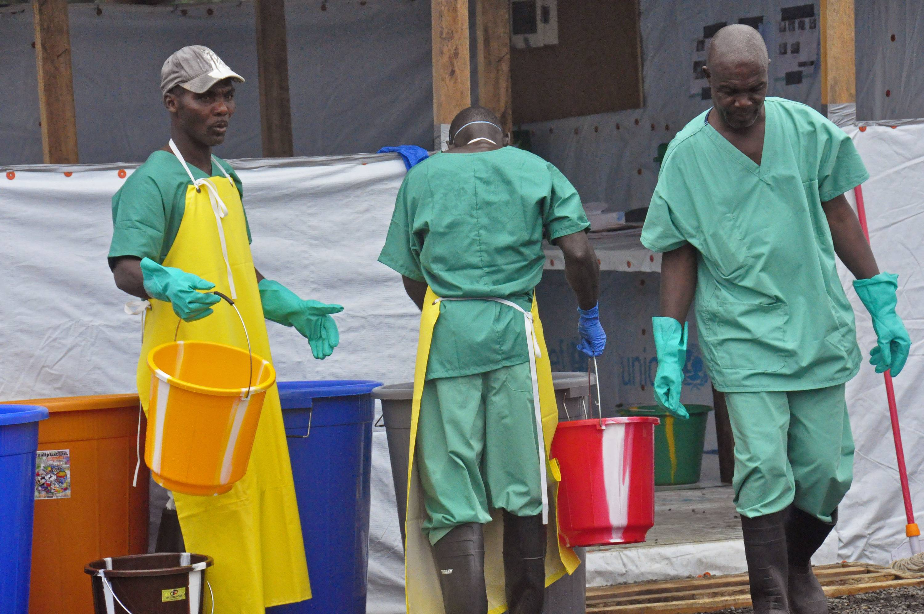Health workers with buckets, as part of their Ebola virus prevention protective gear, at an Ebola treatment center in the city of Monrovia, Liberia, Monday.