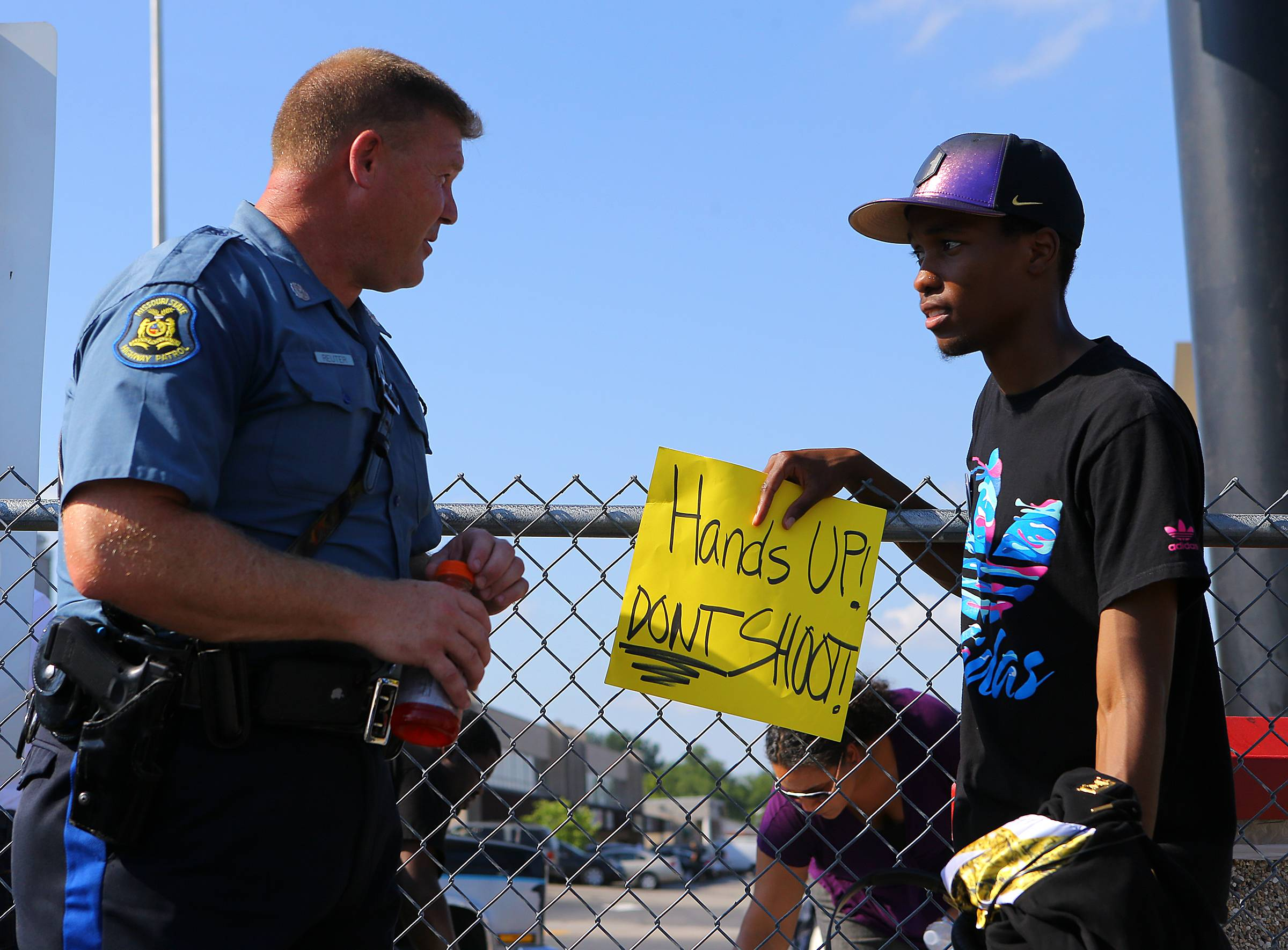 "In an effort to foster some good will Missouri State Higway Patrol trooper D. Reuter chats with protester Robert Clark on Tuesday in Ferguson, Mo. The city of Ferguson says it is working hard to better connect with the community and learn from the ""discord and heartbreak"" that followed the shooting death of 18-year-old Michael Brown by a police officer."