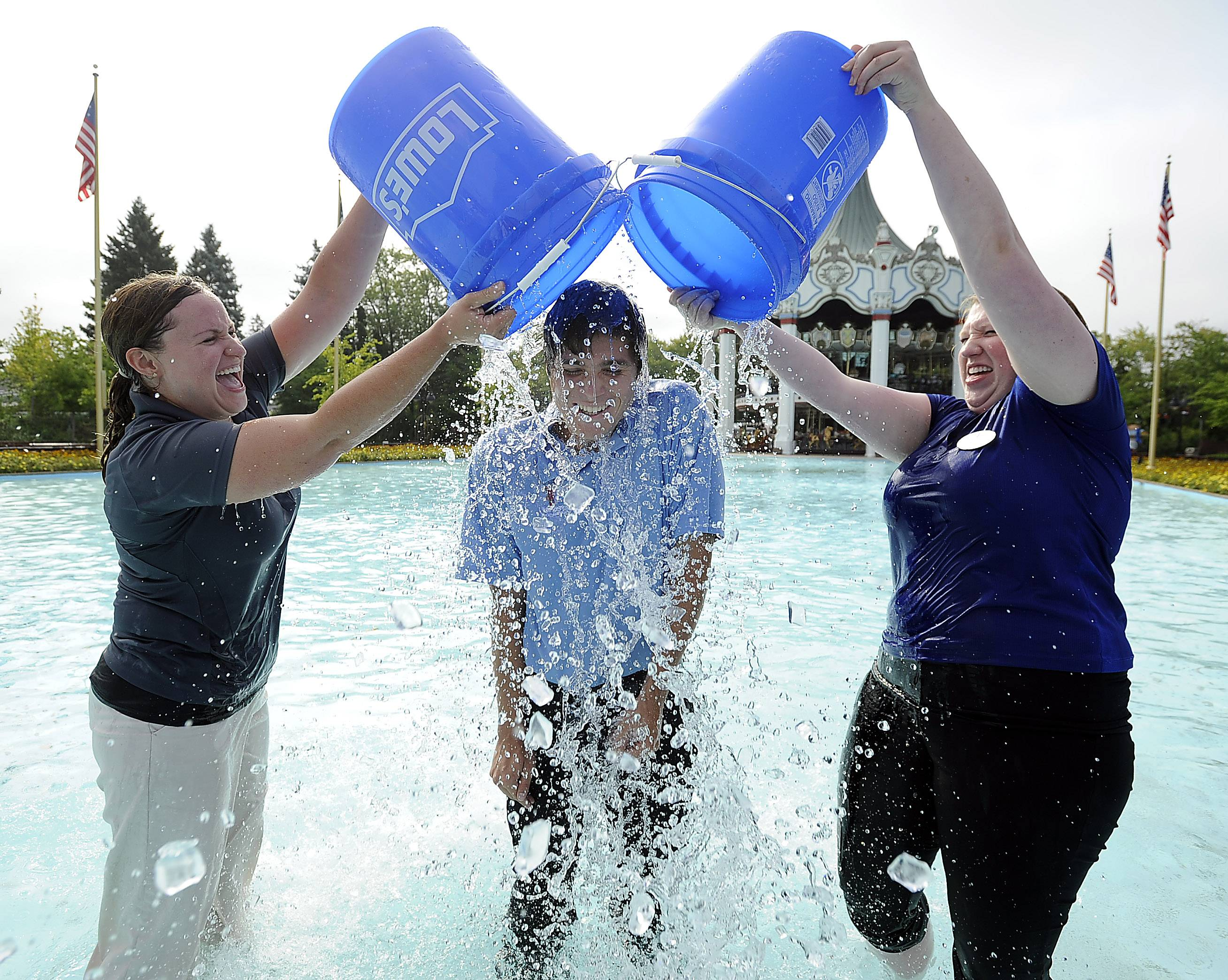 Katy Enrique, Six Flags Great America communications manager, and Tess Claussen, communication specialist, drop buckets of ice water on Dylan Druktenis, 21, of Highwood at the amusement park Monday for the Ice Bucket Challenge.