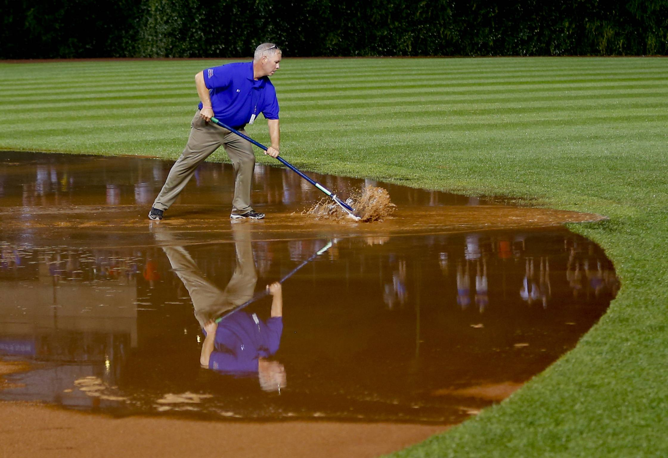 A member of the grounds crew works on the field after a heavy rain soaked Wrigley Field during the fifth inning. But the infield would never dry in time.