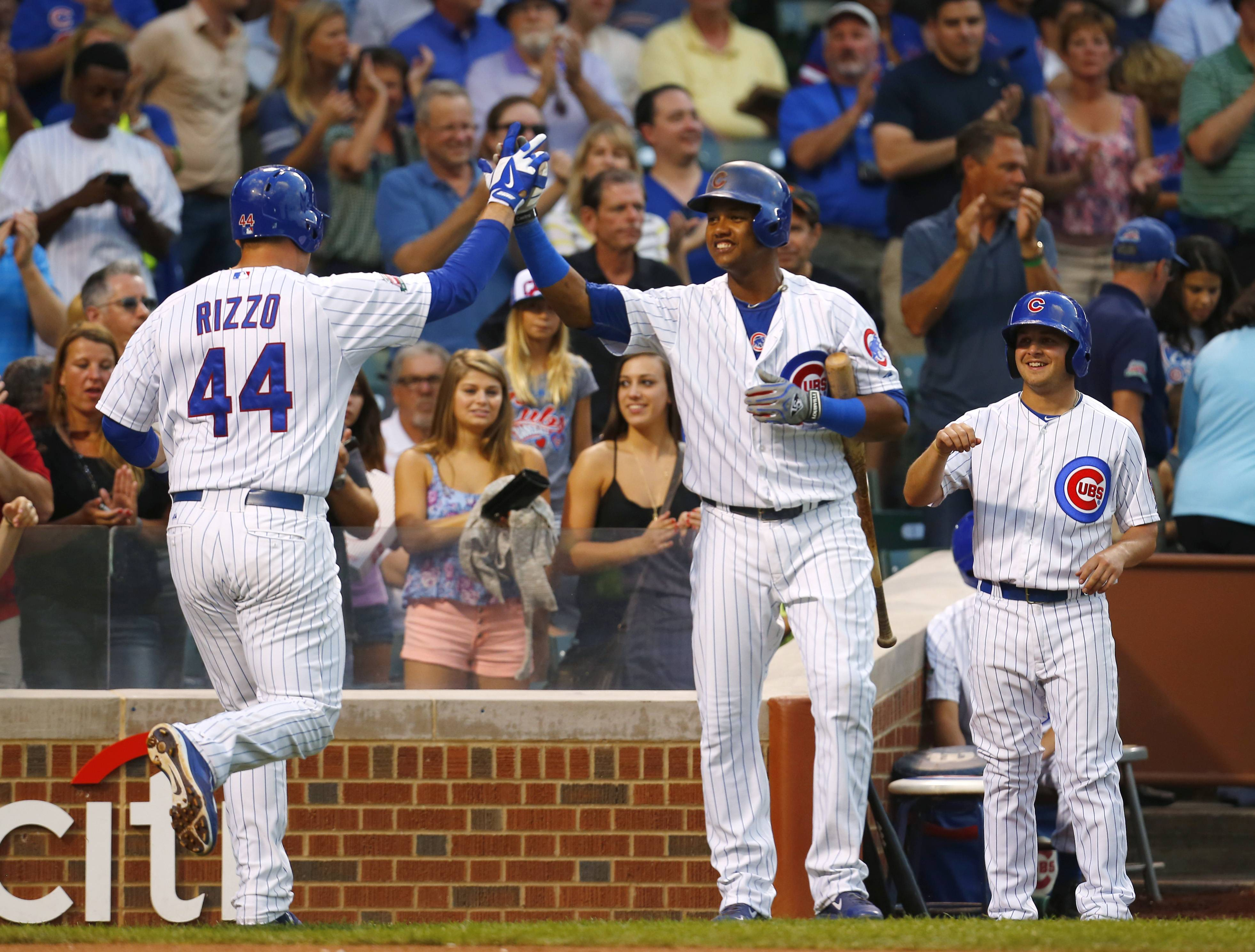 Chicago Cubs' Anthony Rizzo (44) is greeted by teammate Starlin Castro after his 2-run home run against the San Francisco Giants during the first inning.