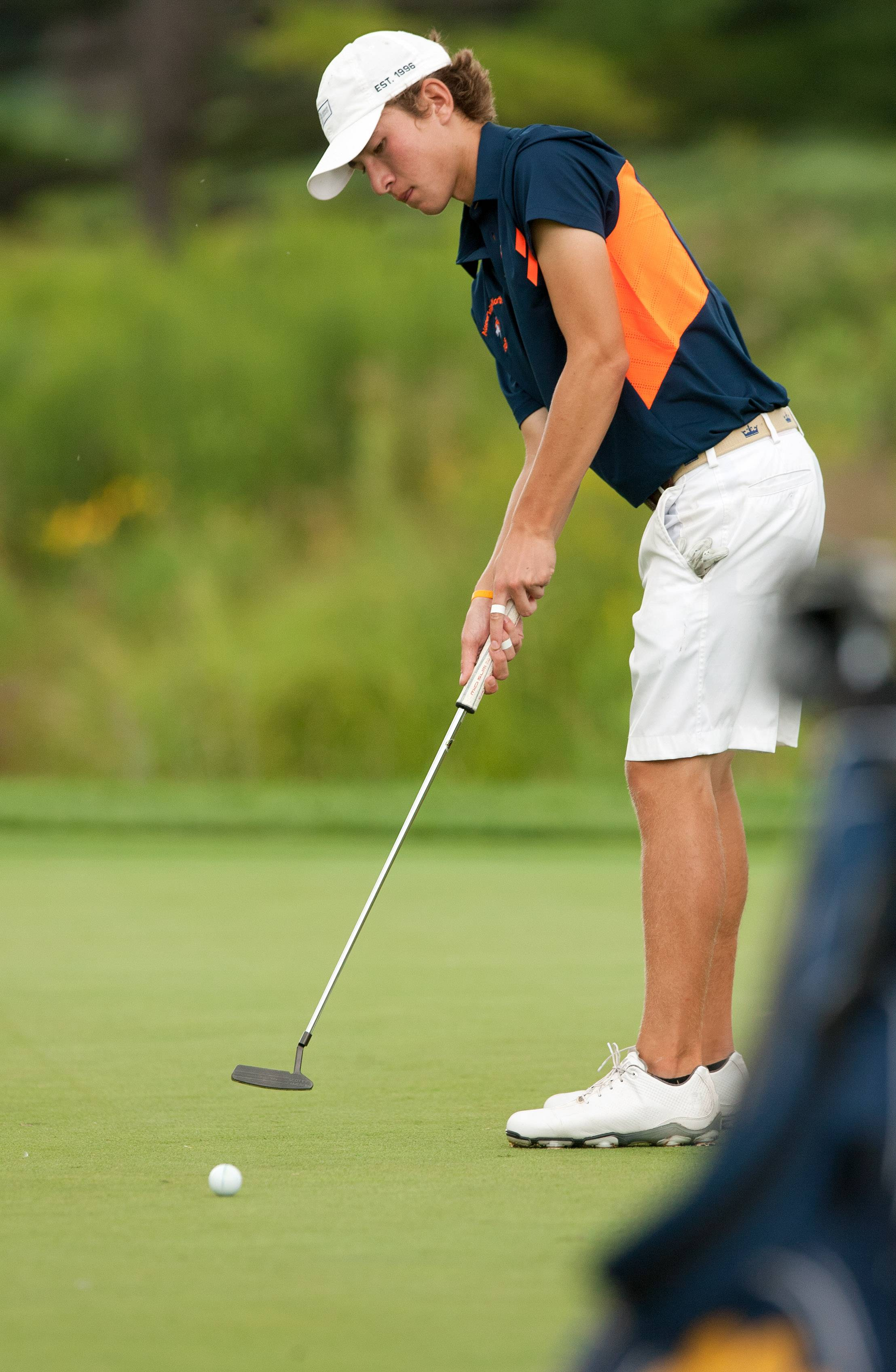 Naperville North's Griffin Brown putts during the Vern McGonagle Memorial High School Golf Championship at the Naperville Country Club.