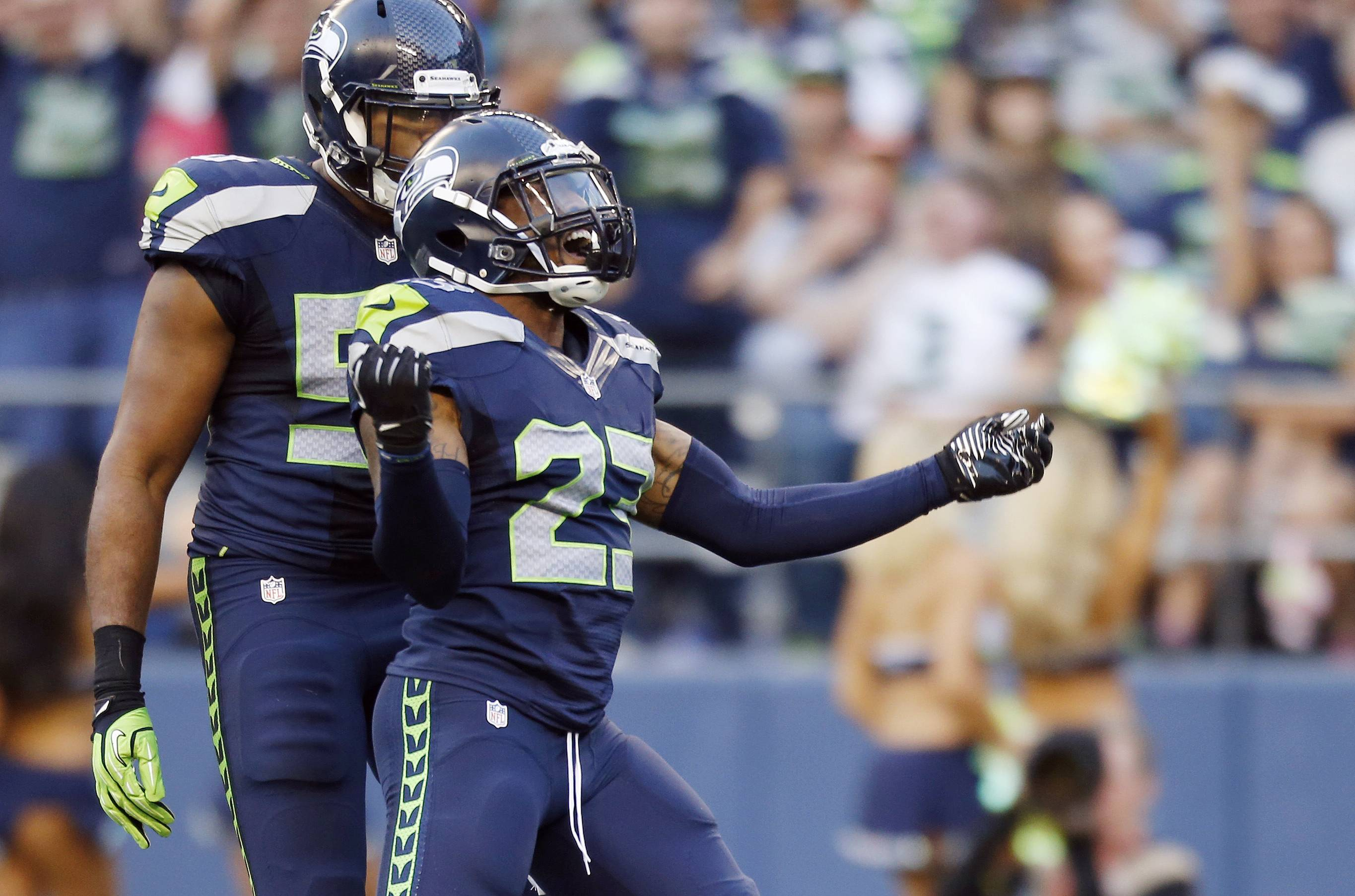 Seahawks strong safety Jeron Johnson (23) celebrates a tackle with outside linebacker K.J. Wright, left, in the first half of a preseason NFL football game against the San Diego Chargers, Friday, Aug. 15, 2014, in Seattle.